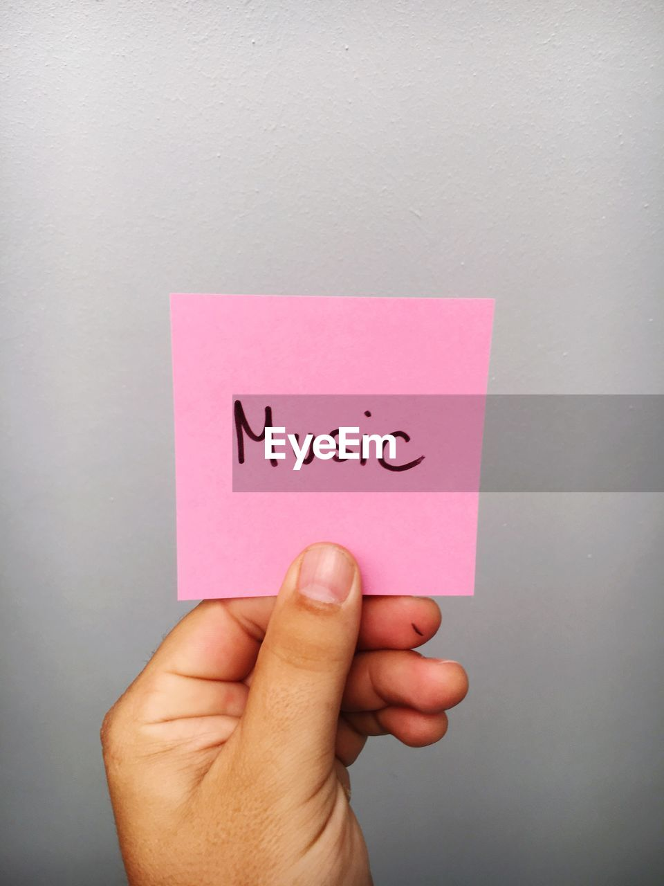 Cropped Hand Of Person Holding Music Text On Adhesive Note Against Gray Background