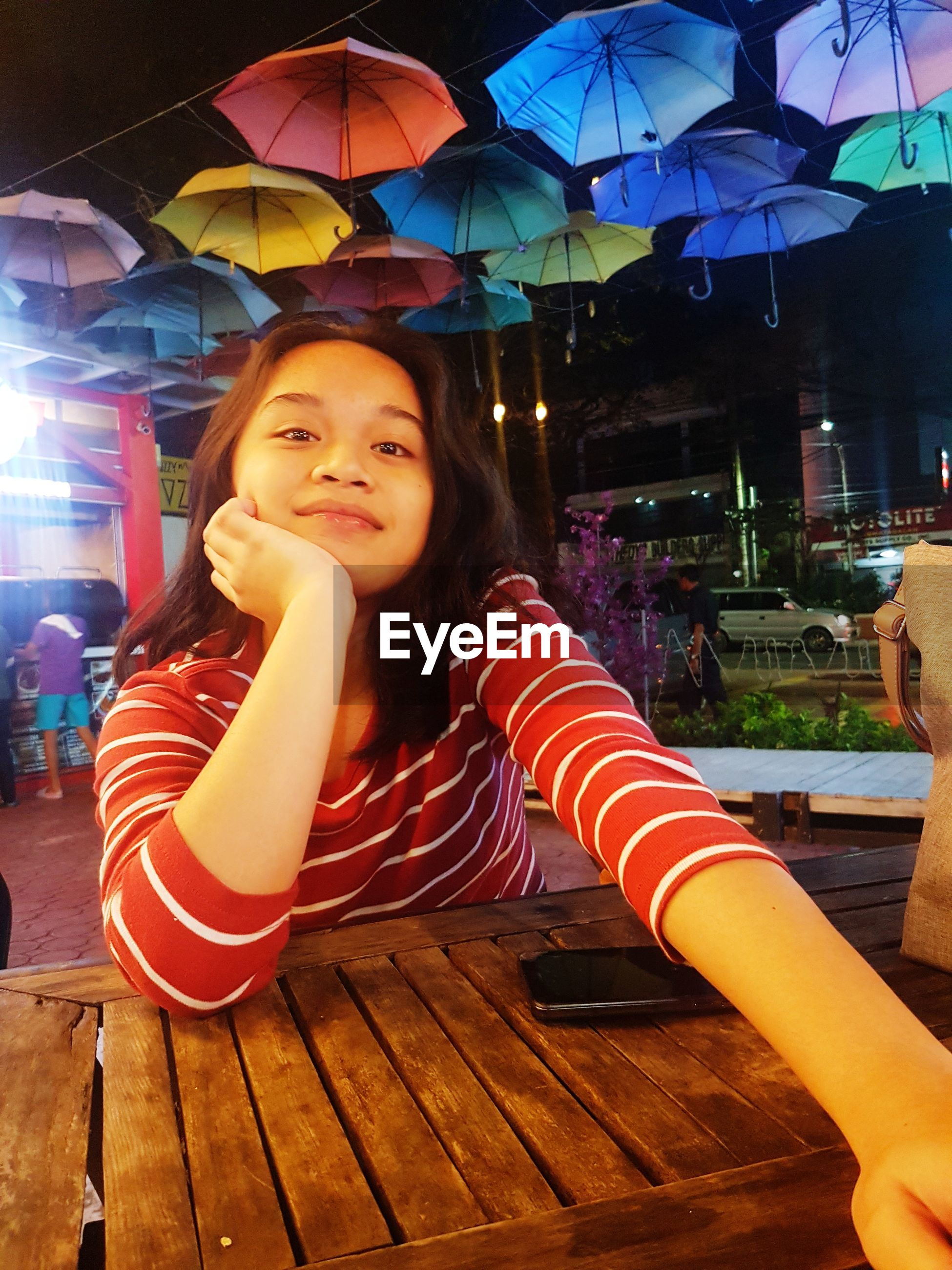 Portrait of smiling teenage girl sitting at restaurant