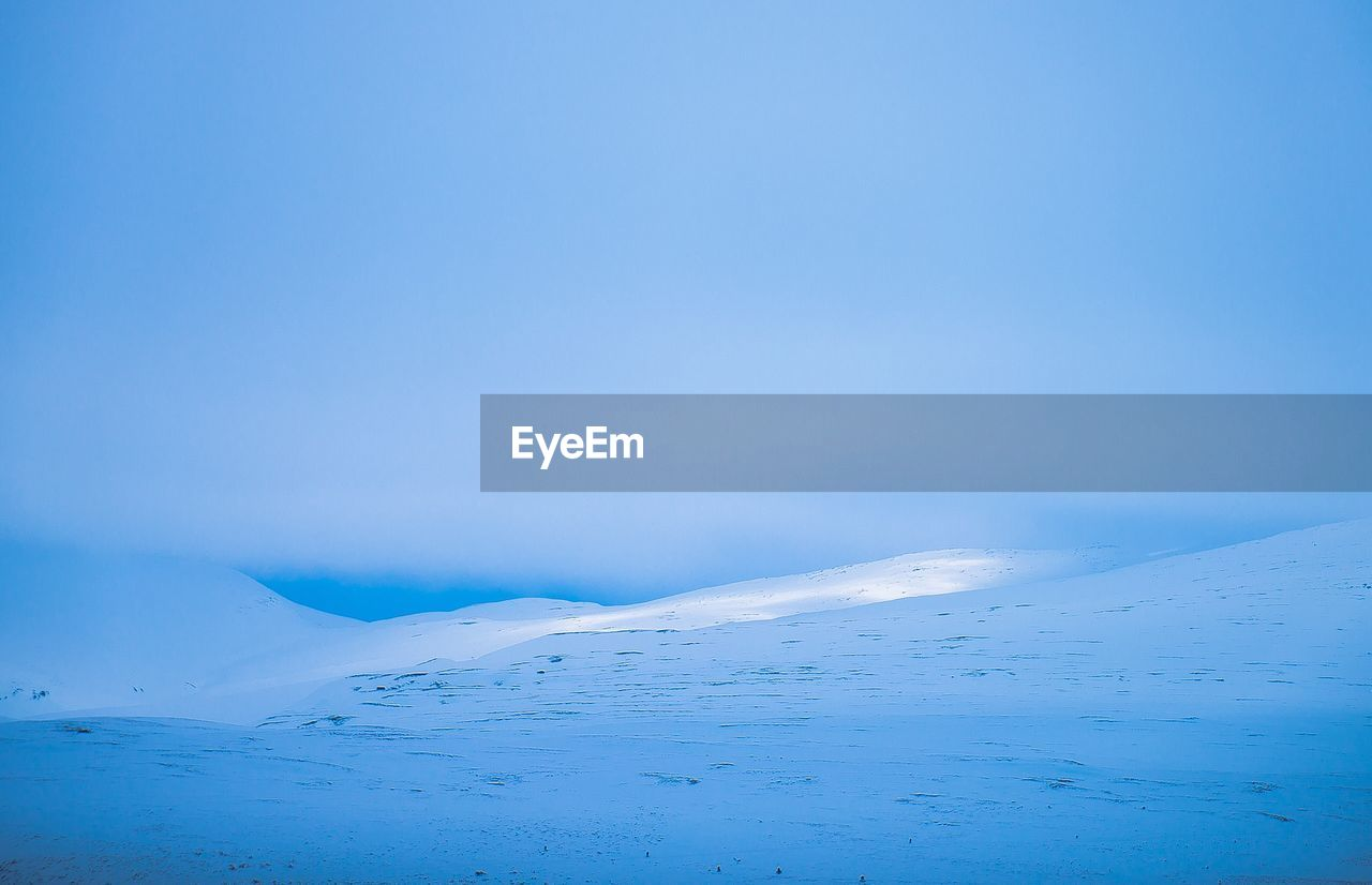SCENIC VIEW OF SNOW COVERED LANDSCAPE AGAINST CLEAR BLUE SKY