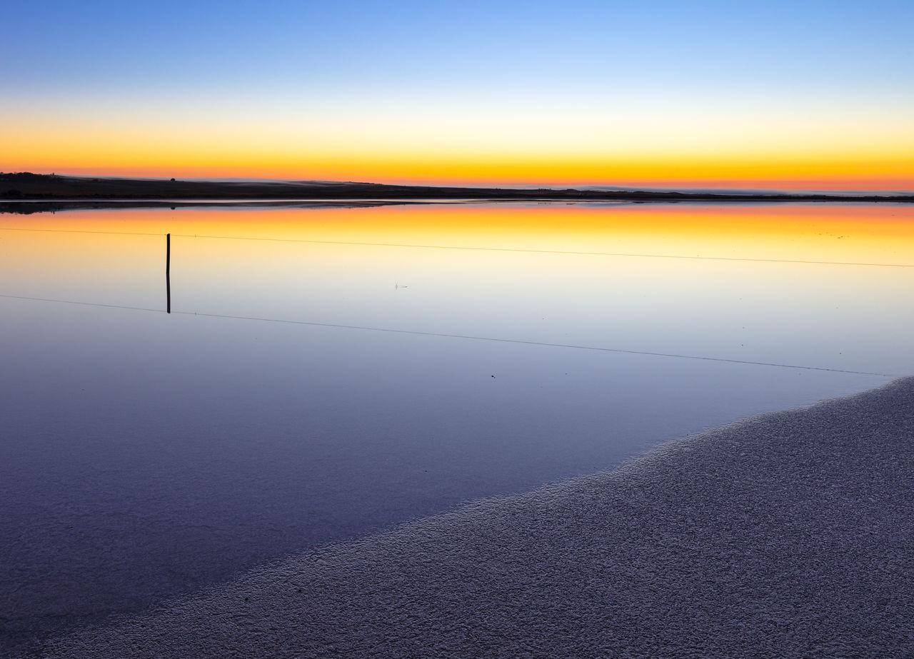 water, sky, scenics - nature, tranquility, beauty in nature, tranquil scene, sunset, beach, sea, nature, land, no people, idyllic, reflection, non-urban scene, salt flat, orange color, outdoors, horizon