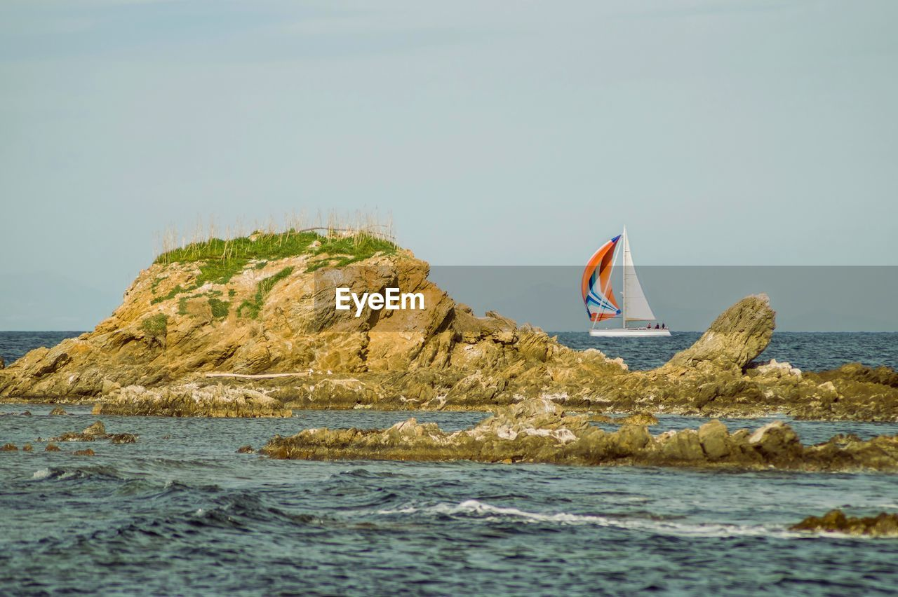 water, sea, waterfront, sky, rock, beauty in nature, nature, day, scenics - nature, rock - object, flag, nautical vessel, mountain, solid, tranquil scene, transportation, land, rock formation, non-urban scene, no people, sailboat, outdoors, wind