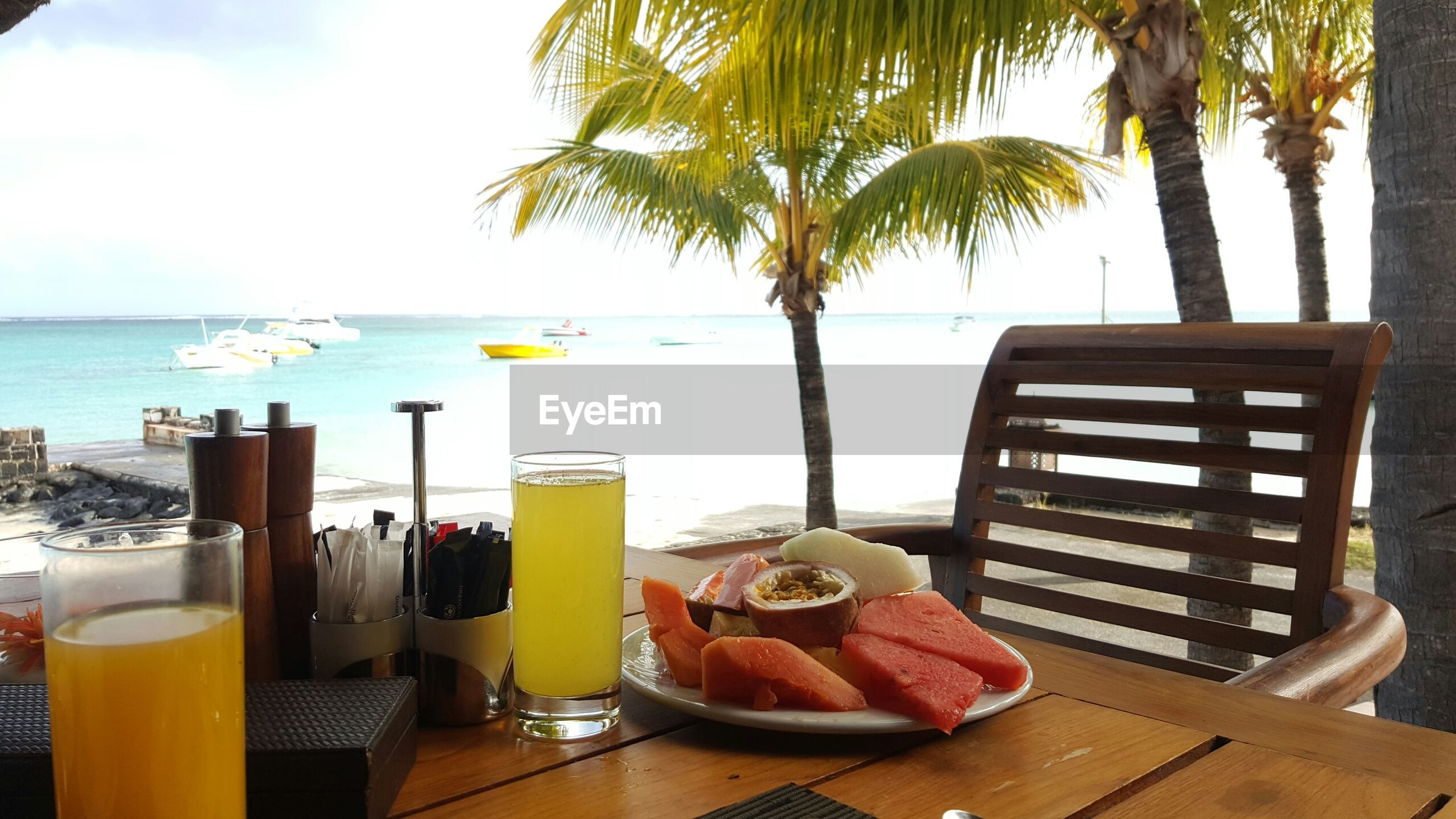 Fruits and juices served on table at beach restaurant