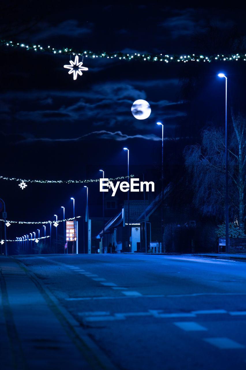 ILLUMINATED STREET LIGHTS AGAINST SKY
