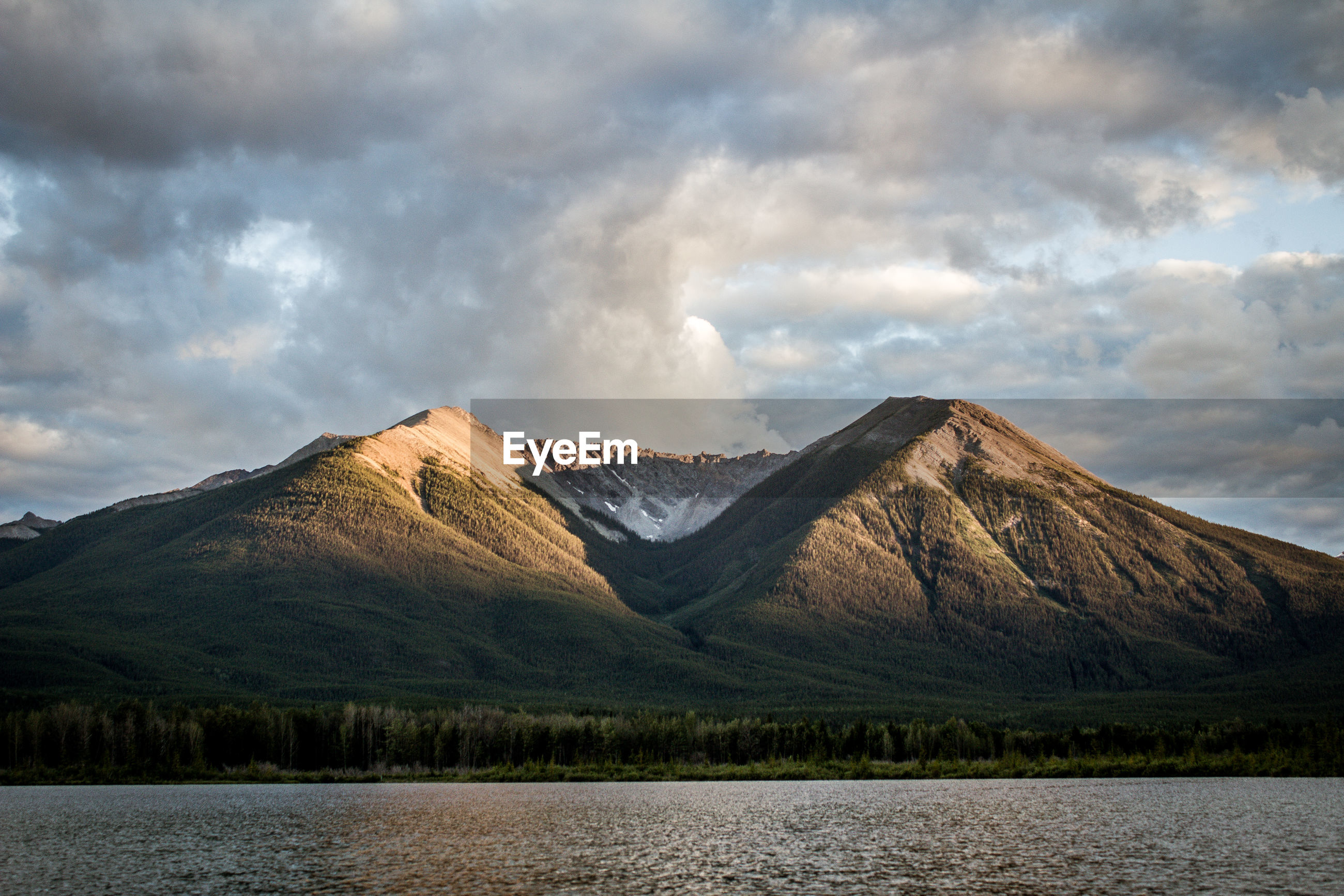 View of lake by mountains against cloudy sky