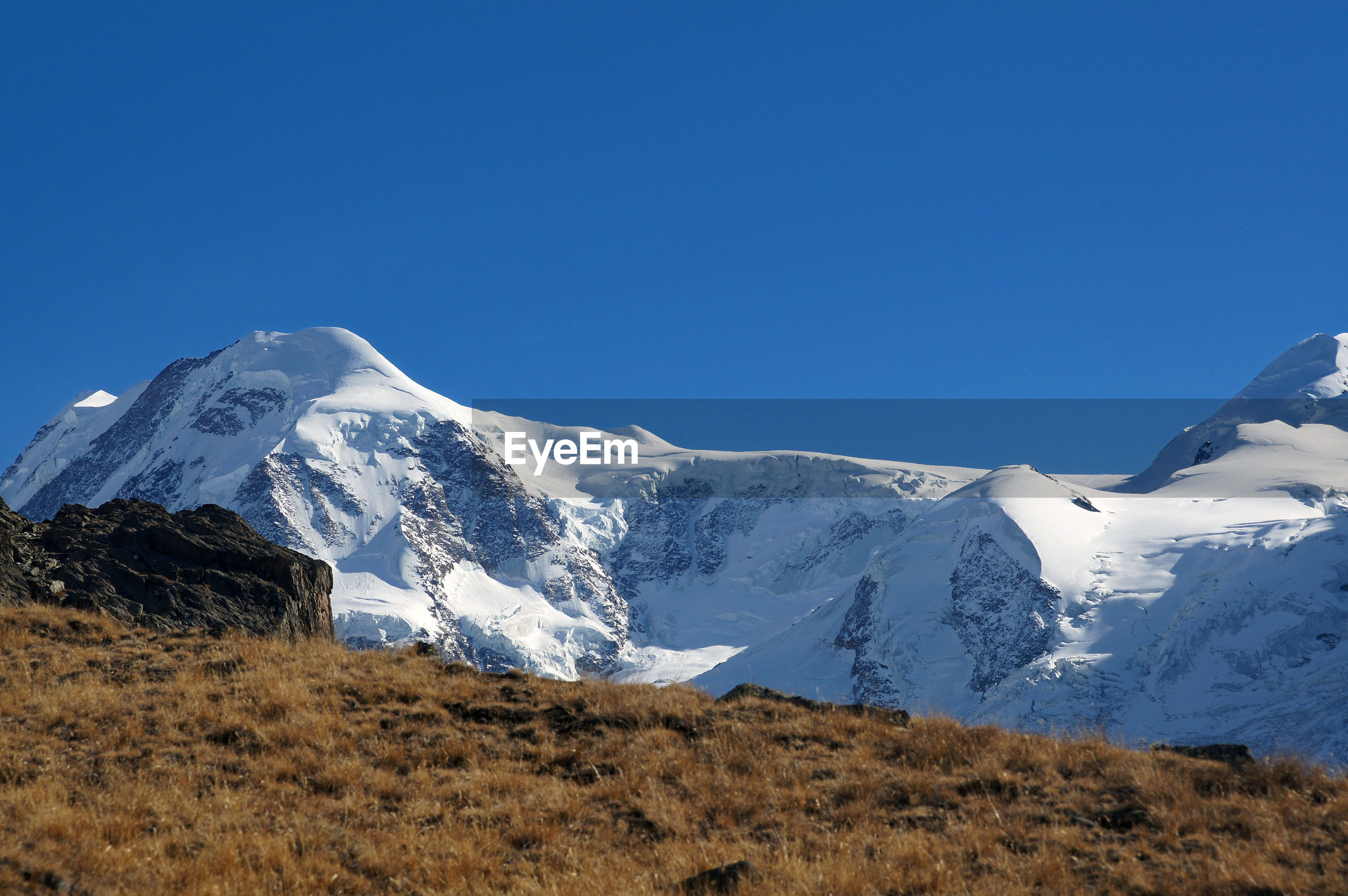 SNOWCAPPED MOUNTAINS AGAINST CLEAR BLUE SKY