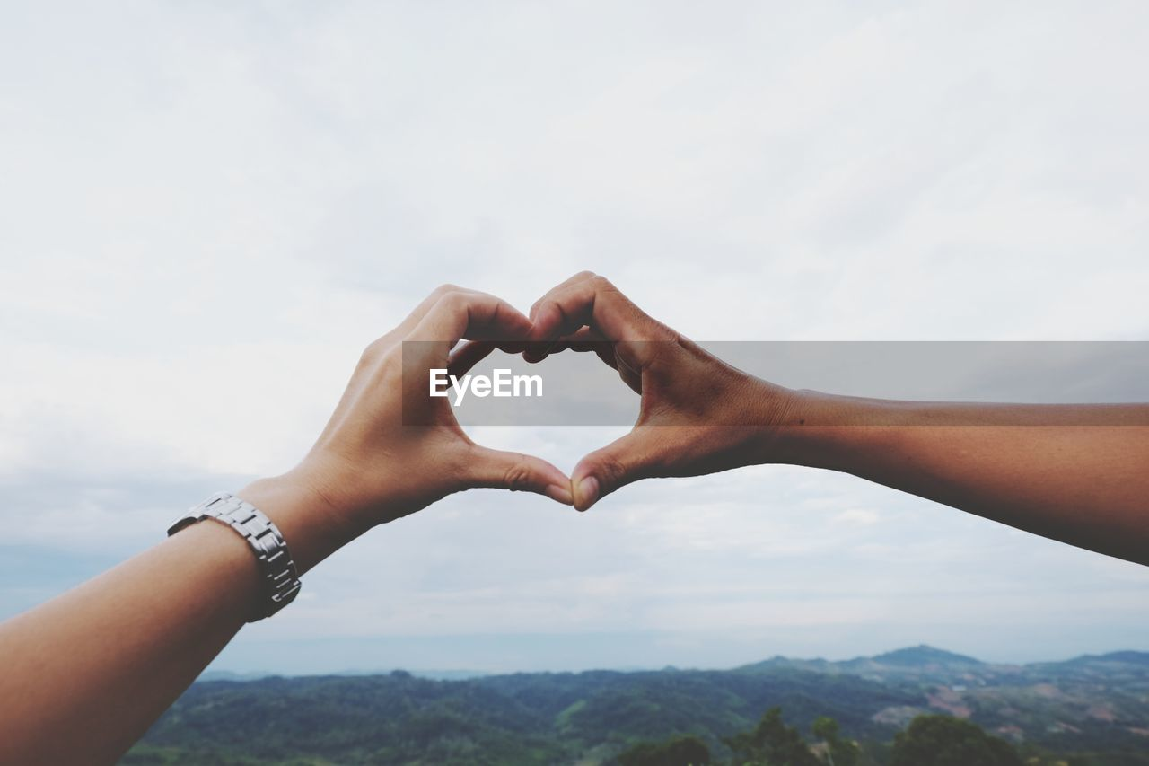 Cropped Image Of Couple Forming Heart Shape From Hands Against Sky