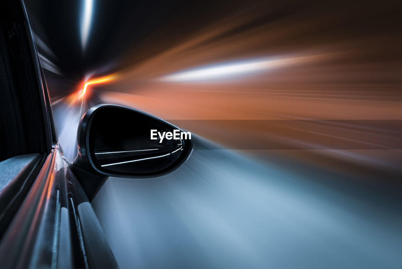 Light trails on side-view mirror. motion blur, electric mobility