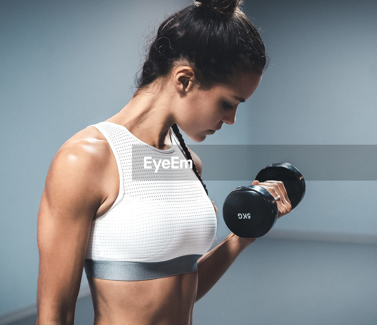 one person, lifestyles, indoors, sports training, healthy lifestyle, exercising, strength, sport, young adult, sports clothing, standing, dumbbell, holding, young women, weights, front view, adult, weight, weight training, body conscious