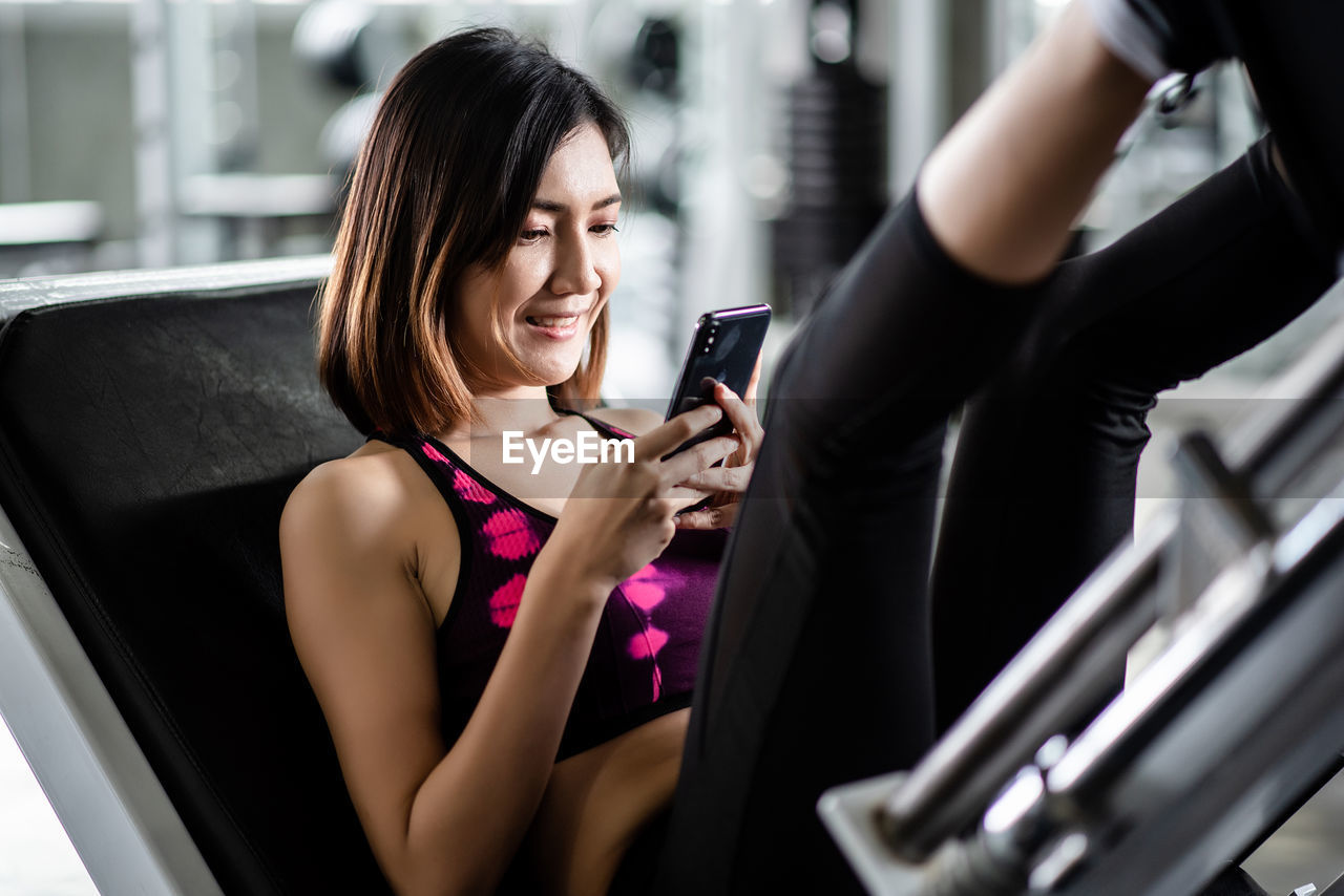 Woman using mobile phone while exercising in gym