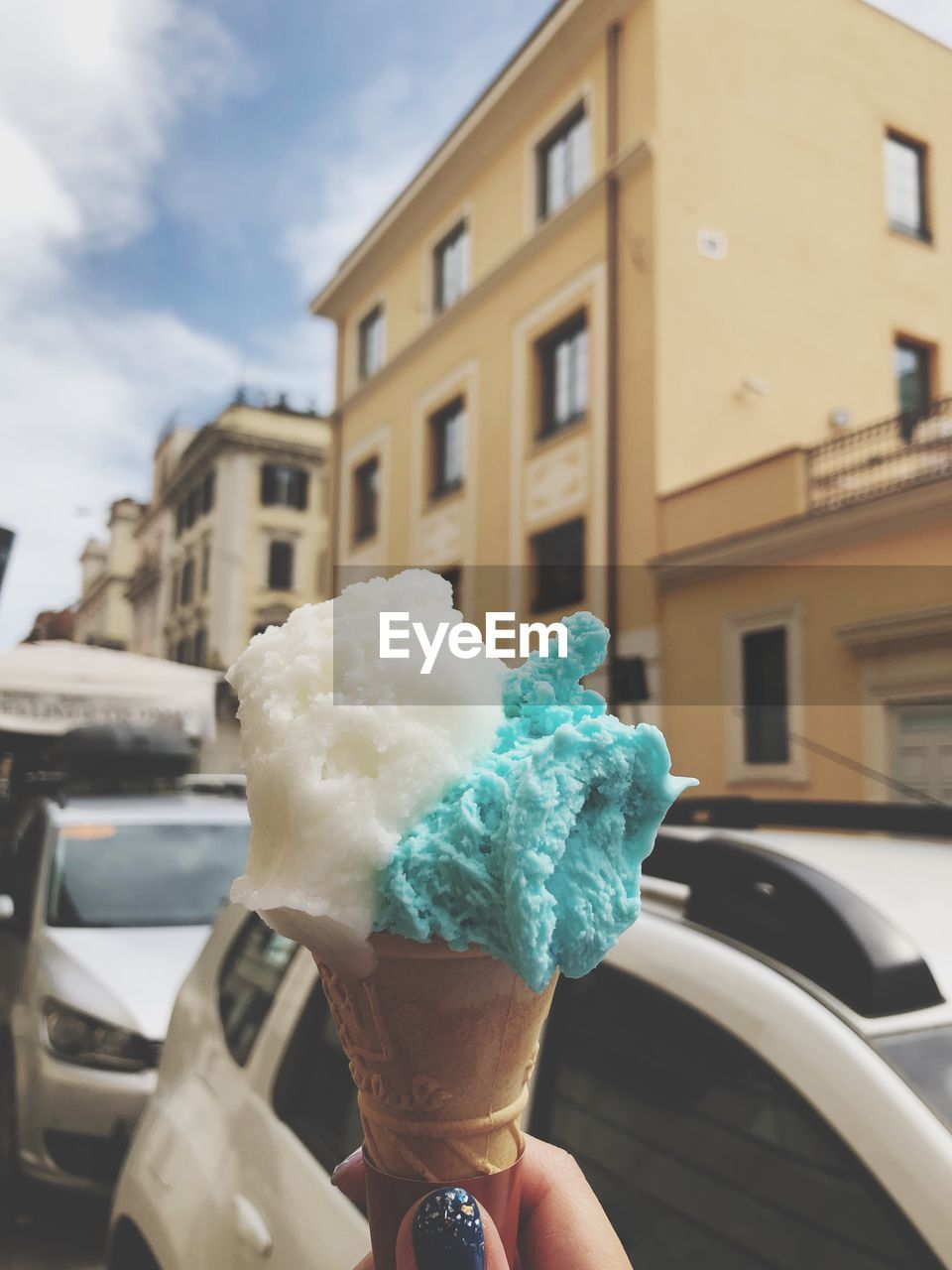 human hand, hand, sweet food, sweet, car, real people, transportation, mode of transportation, holding, human body part, one person, ice cream cone, dairy product, ice cream, motor vehicle, day, building exterior, frozen food, architecture, indulgence, temptation, outdoors, finger