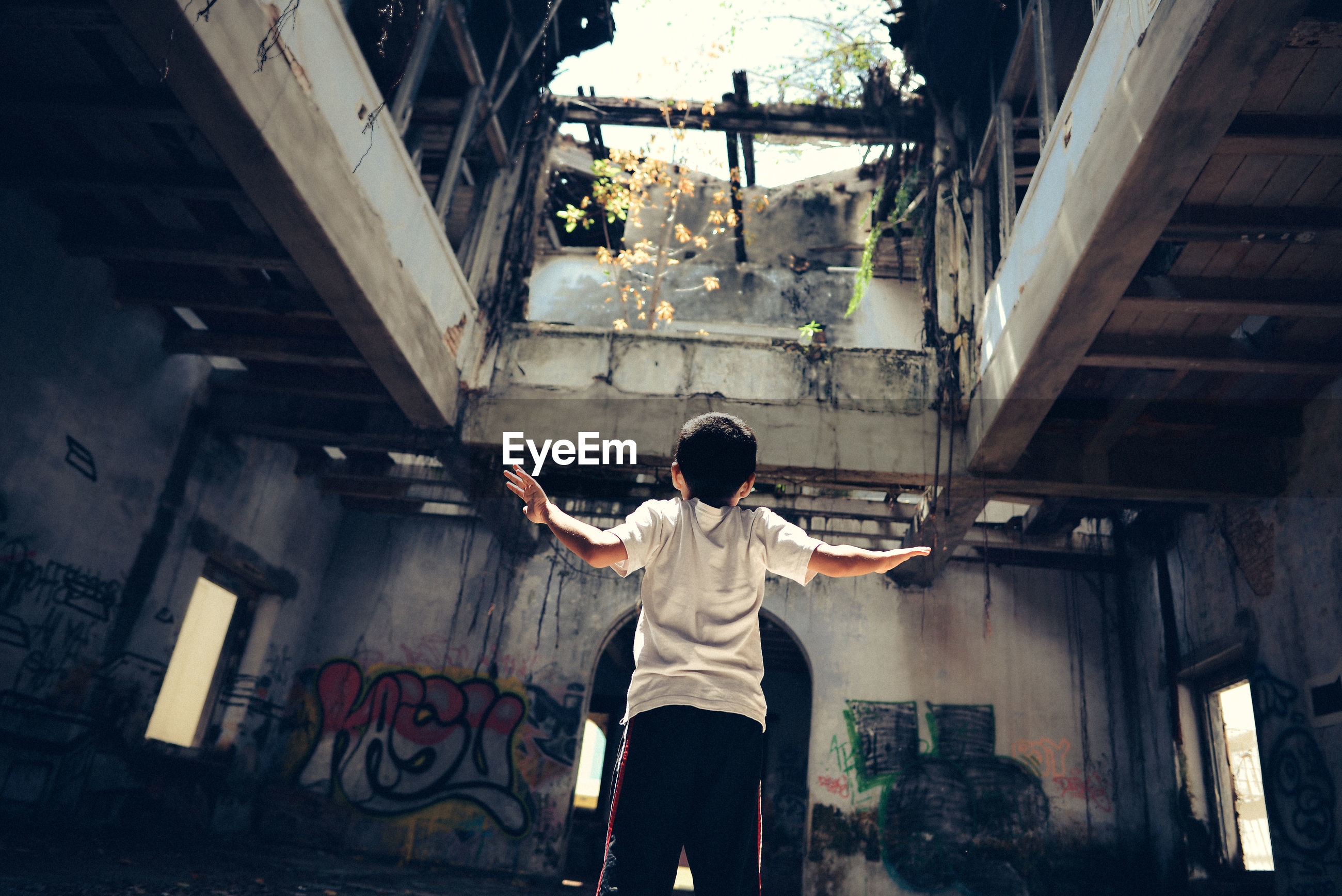 Rear view of boy standing at abandoned building