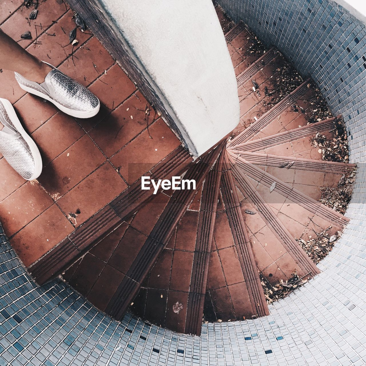 Low Section Of Person Standing On Spiral Staircase