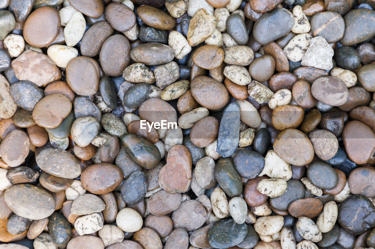 large group of objects, rock, pebble, stone, solid, full frame, abundance, stone - object, backgrounds, nature, day, no people, land, rock - object, high angle view, textured, directly above, beach, outdoors, variation