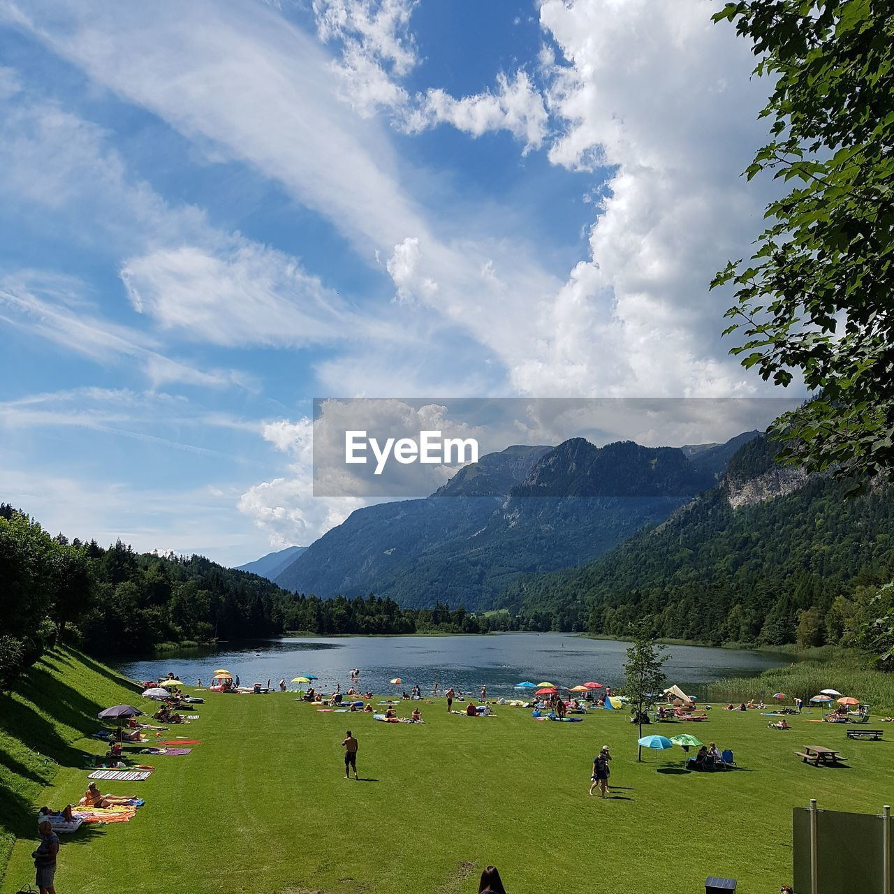 cloud - sky, sky, plant, beauty in nature, scenics - nature, mountain, group of people, nature, tree, day, water, leisure activity, grass, real people, land, crowd, idyllic, large group of people, relaxation, outdoors