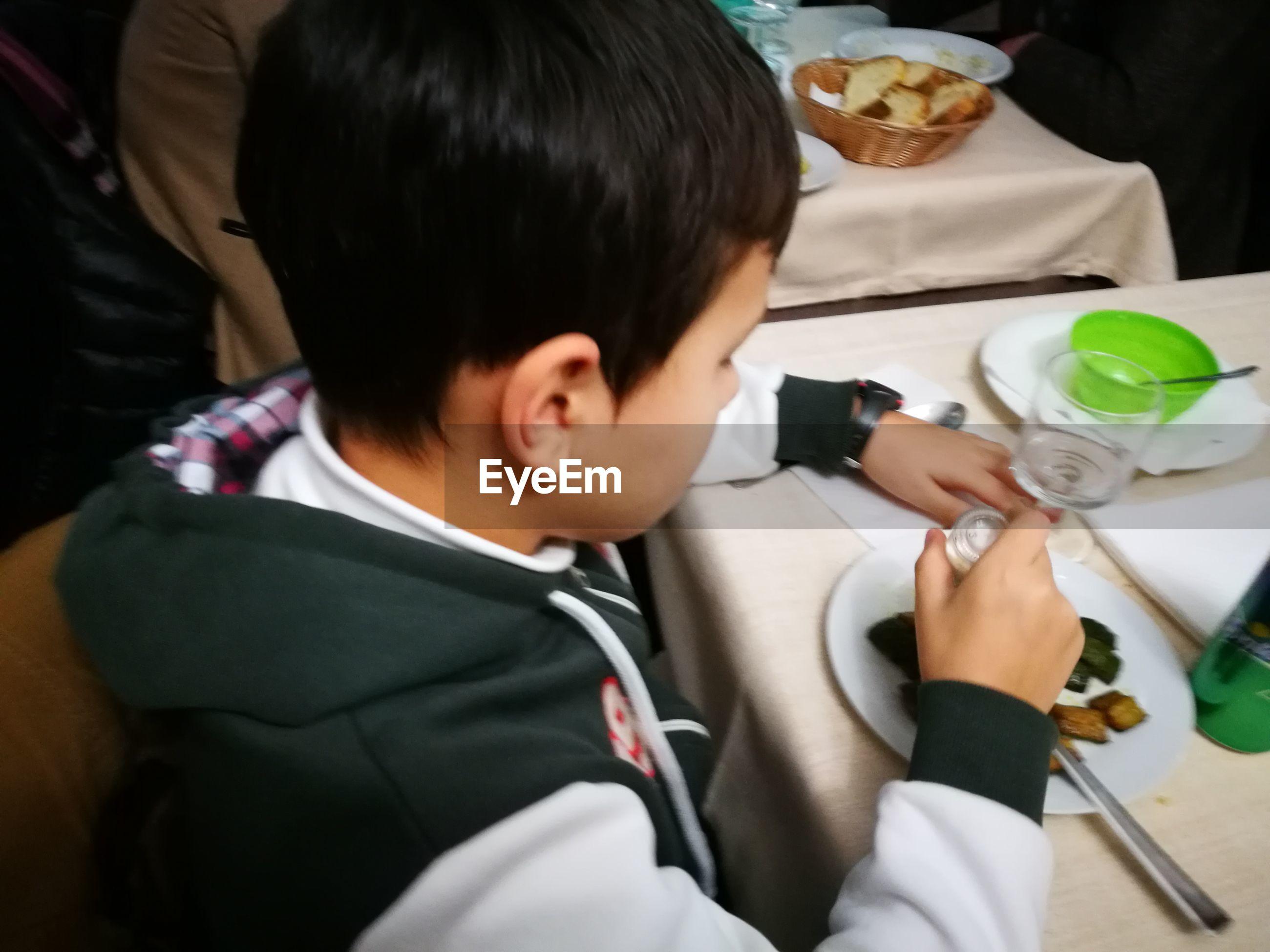 Close-up of boy having food at restaurant