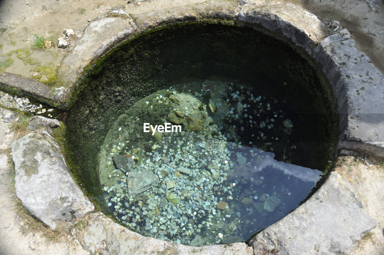 water, high angle view, no people, nature, drain, circle, geometric shape, solid, outdoors, close-up, stone - object, metal, day, well, architecture, sewage, pipe - tube, built structure, hole, purity
