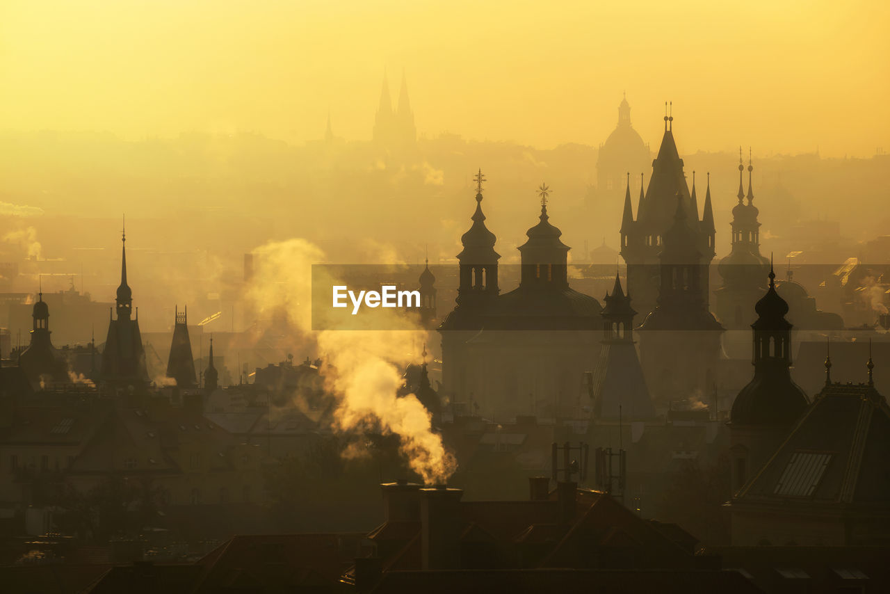 building exterior, built structure, architecture, building, sky, religion, place of worship, belief, spirituality, sunset, nature, no people, travel destinations, orange color, city, fog, tower, outdoors, cityscape, pollution, spire