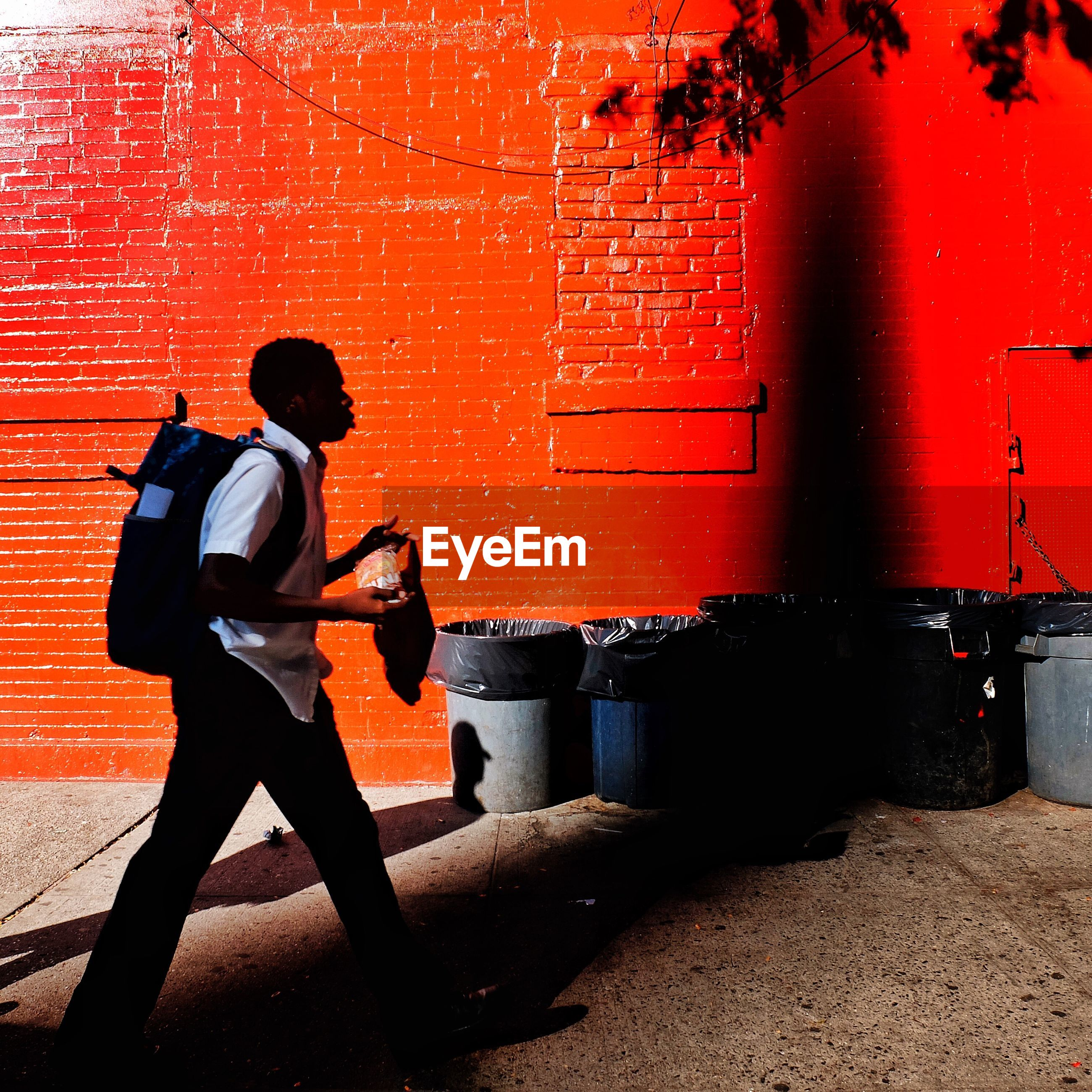 FULL LENGTH SIDE VIEW OF MAN WALKING ON RED WALL