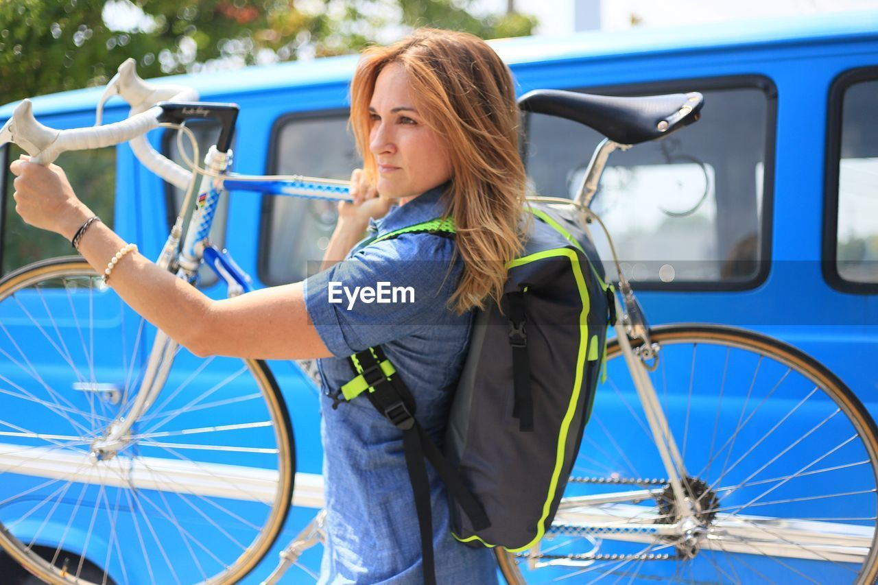 Woman Carrying Bicycle While Looking Away