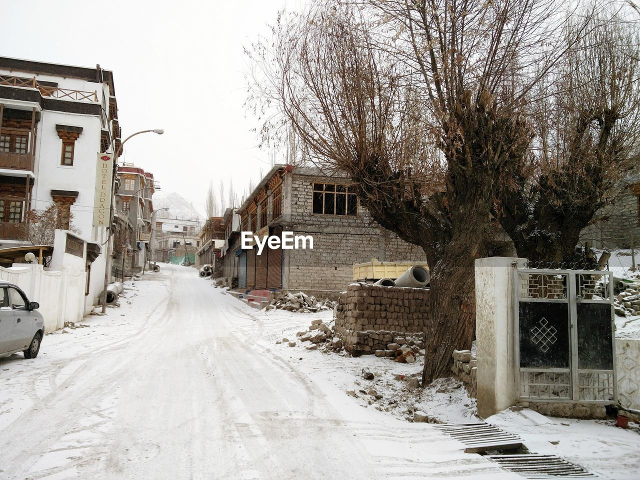 cold temperature, winter, snow, building exterior, architecture, built structure, building, tree, transportation, city, residential district, road, nature, bare tree, sky, the way forward, day, direction, street, no people, snowing, outdoors, extreme weather, blizzard