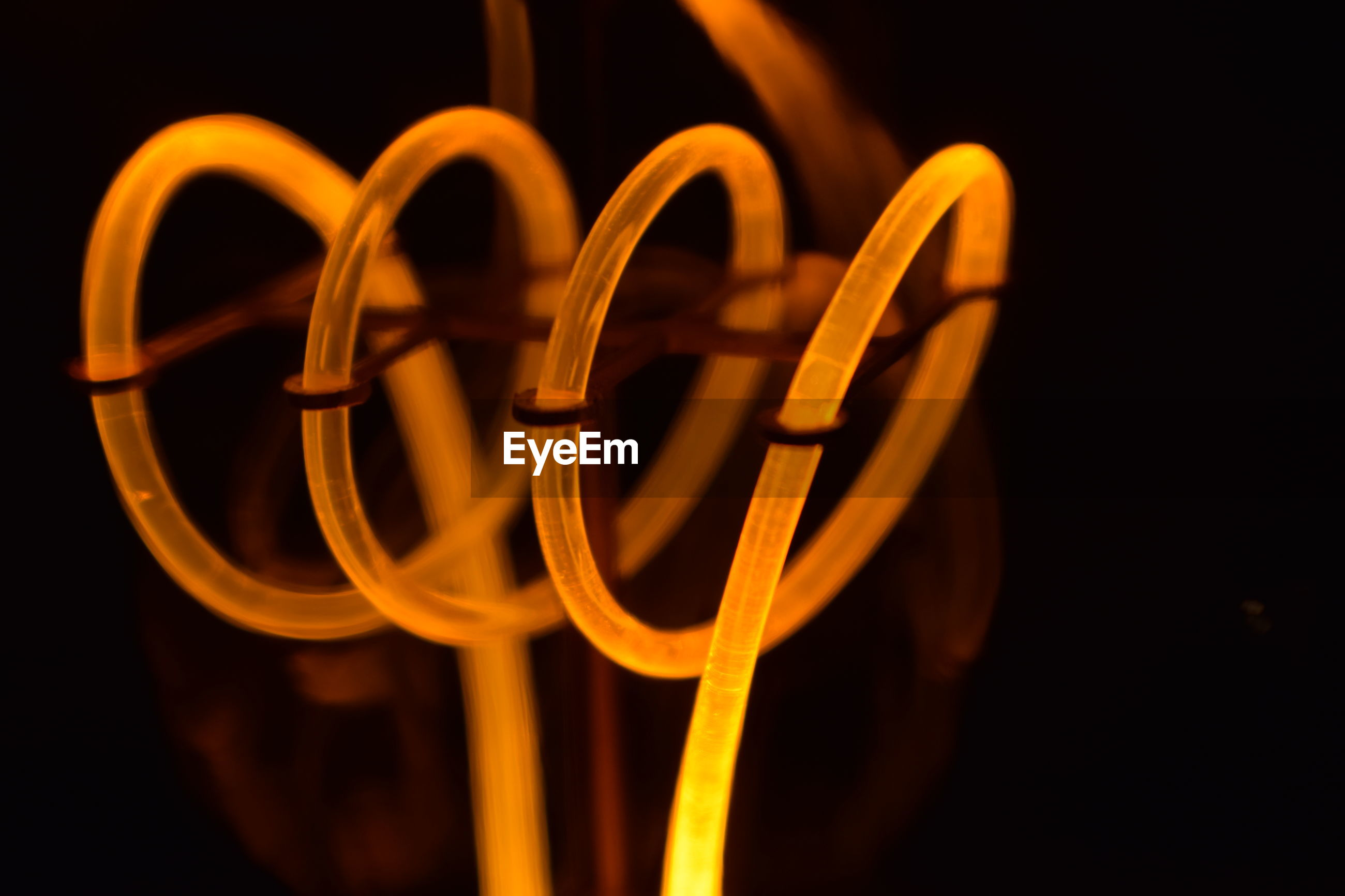 Close-up of illuminated fiber optic cable against black background