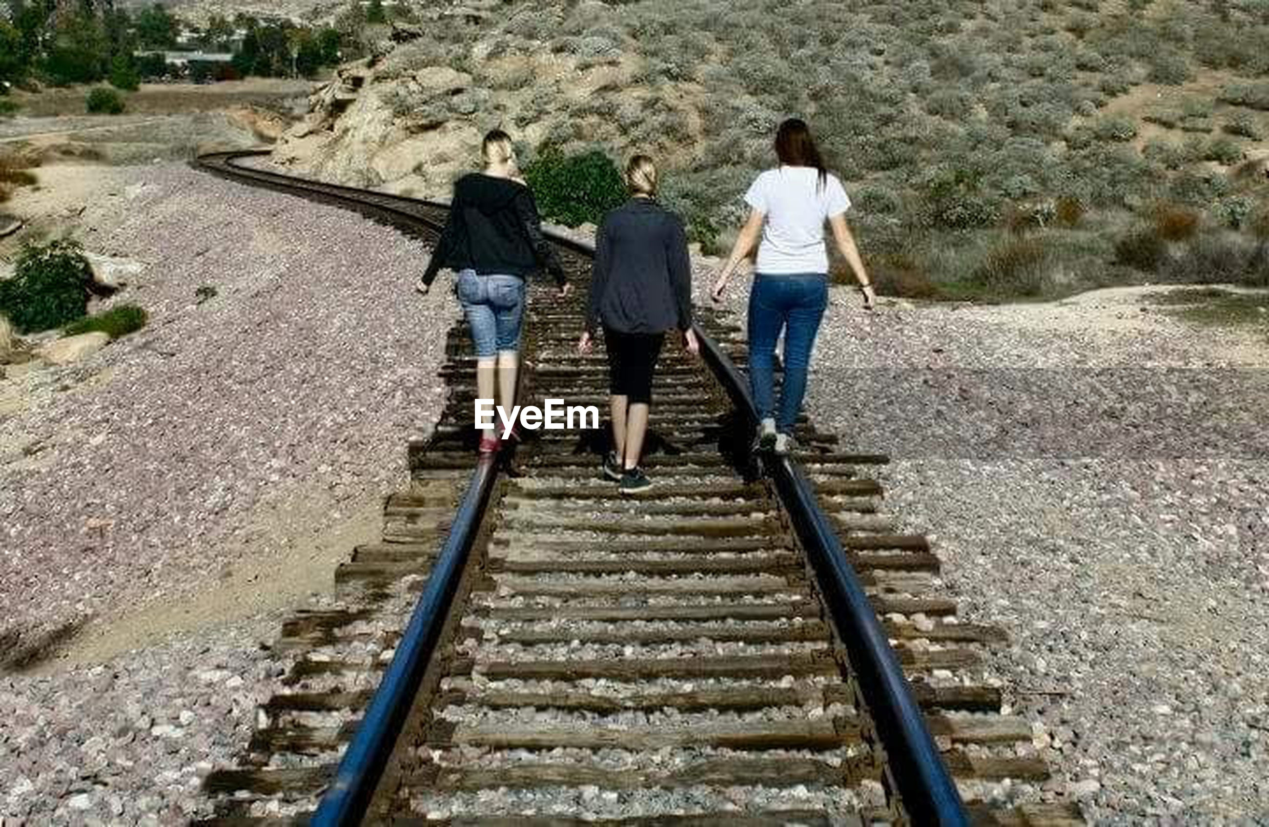 railroad track, the way forward, men, lifestyles, full length, walking, leisure activity, steps, rear view, transportation, person, rail transportation, high angle view, travel, rock - object, vanishing point, diminishing perspective