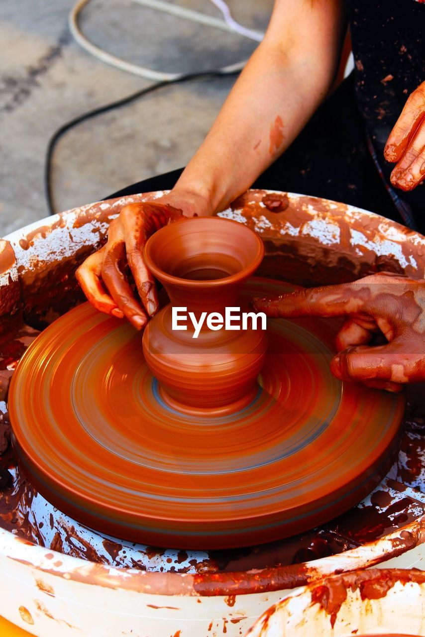 People Making Pottery On Wheel