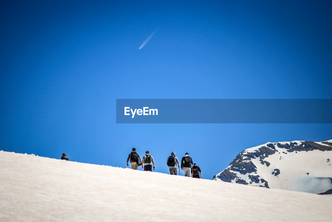 Low Angle View Of Male Hikers Hiking On Snowcapped Mountain