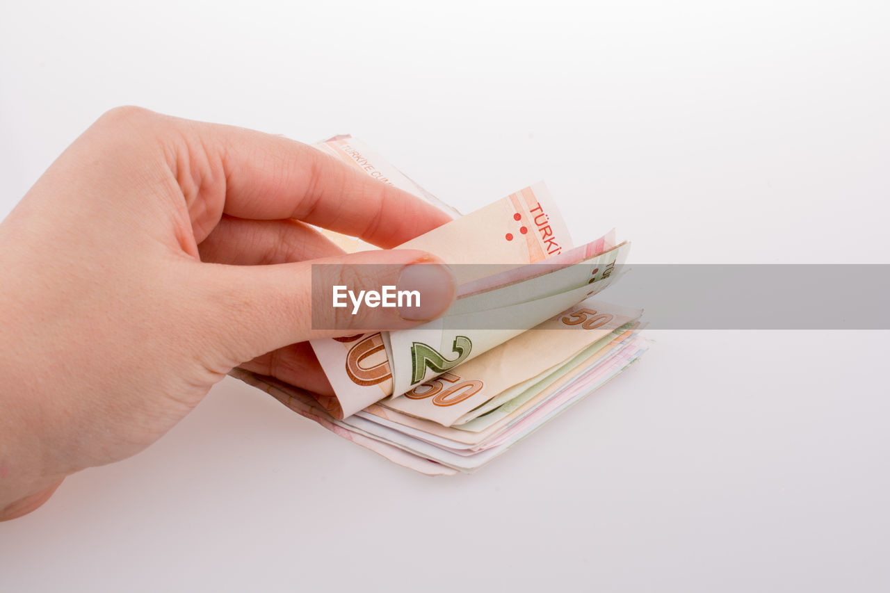 human hand, hand, holding, human body part, studio shot, currency, one person, finance, paper currency, copy space, indoors, white background, unrecognizable person, wealth, business, real people, savings, body part, close-up, finger, economy