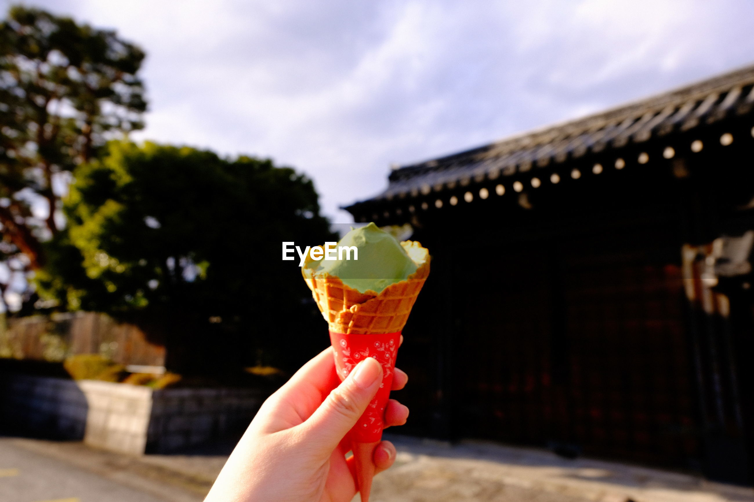 Cropped hand having ice cream cone against built structure