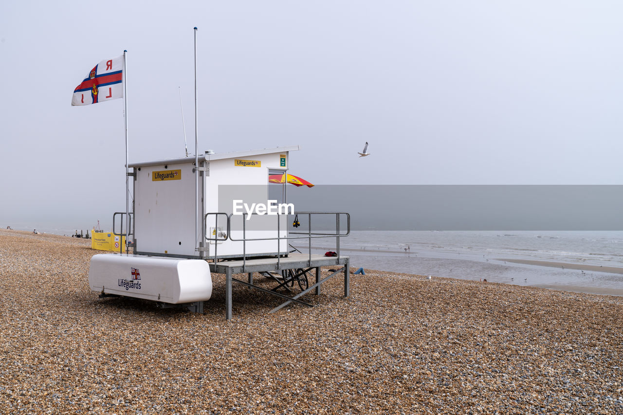 land, water, beach, sea, nature, sky, lifeguard hut, hut, day, sand, flag, no people, man made structure, safety, security, protection, architecture, beauty in nature, built structure, outdoors, horizon over water