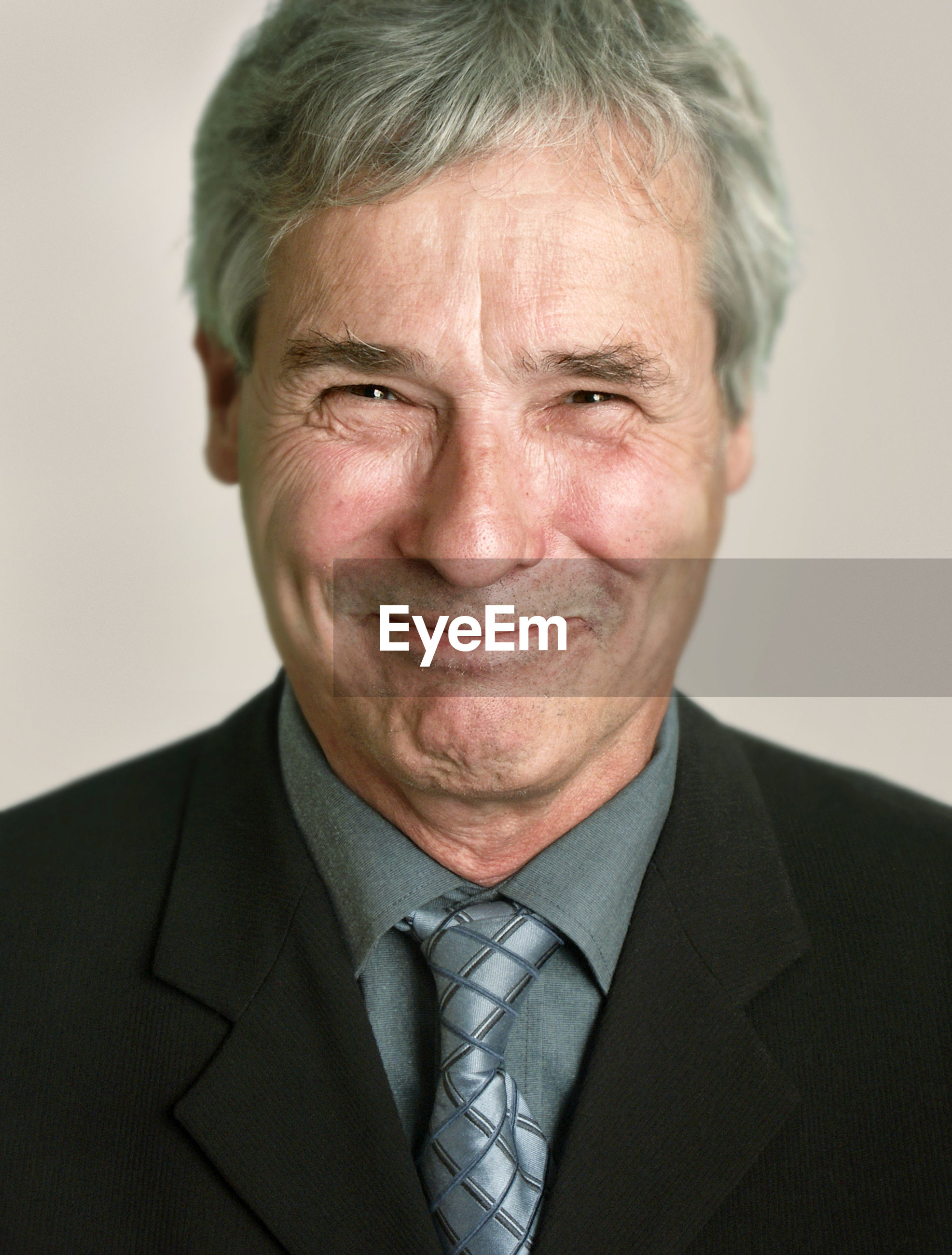 Close-up portrait of smiling senior man against gray background
