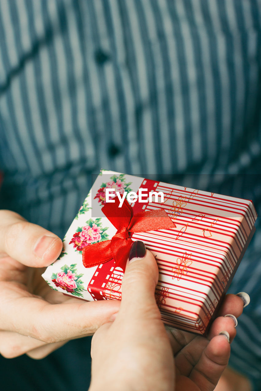 Cropped Hand Giving Gift To Man