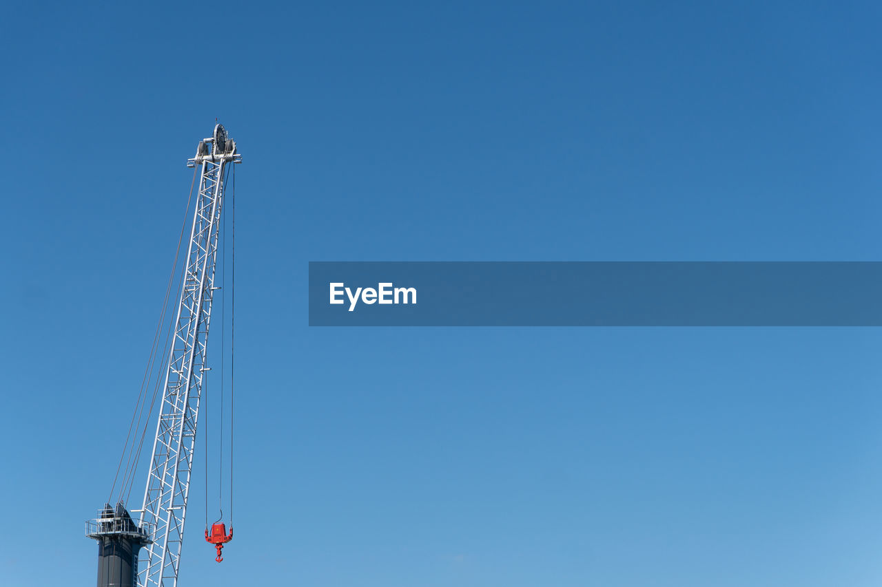 low angle view, blue, sky, copy space, tower, clear sky, built structure, architecture, no people, tall - high, construction industry, day, crane - construction machinery, machinery, nature, communication, industry, construction site, development, outdoors, global communications, construction equipment