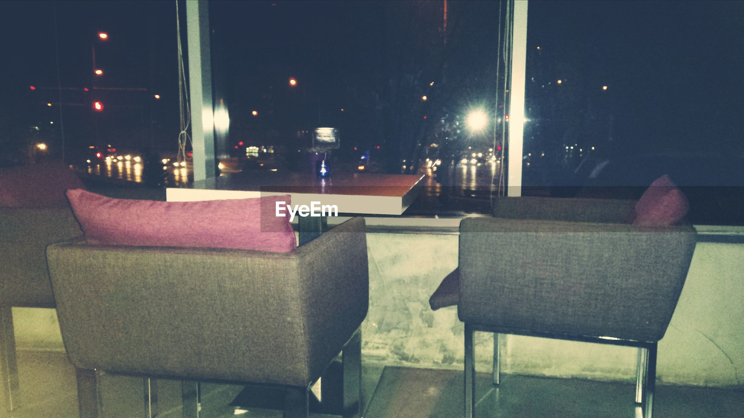 chair, illuminated, table, empty, lighting equipment, night, absence, architecture, built structure, building exterior, street light, restaurant, indoors, window, bench, seat, city, house, glass - material, no people