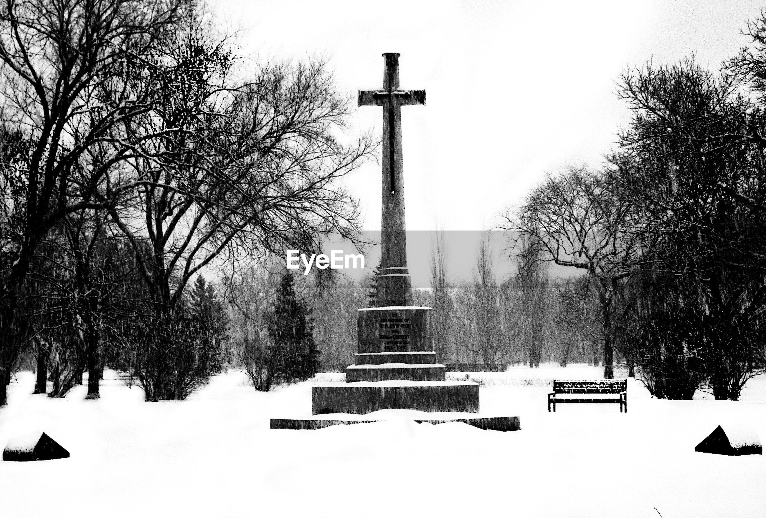 Low angle view of cross on snow covered field