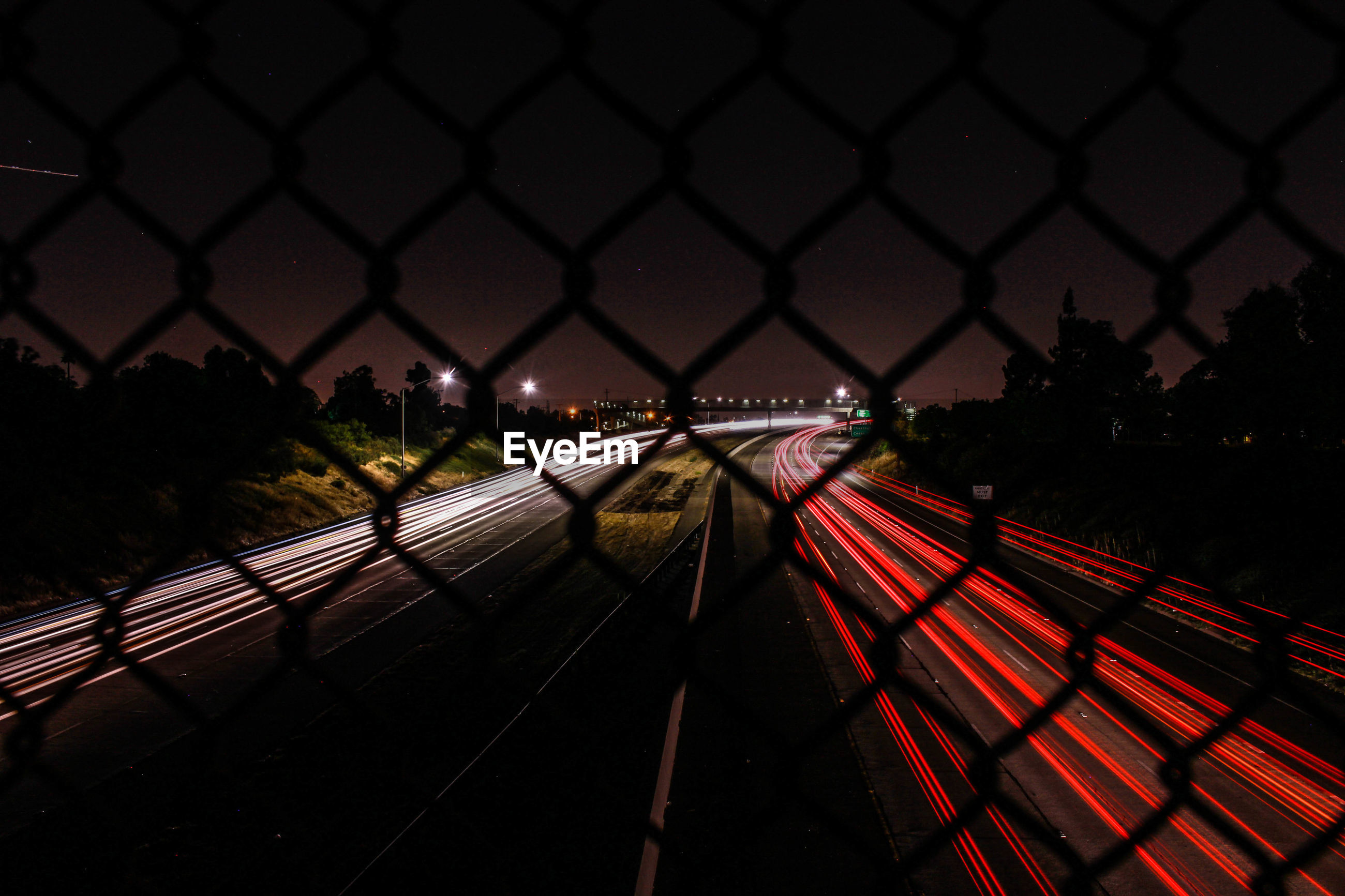 Light trail on highway against sky seen from chainlink fence
