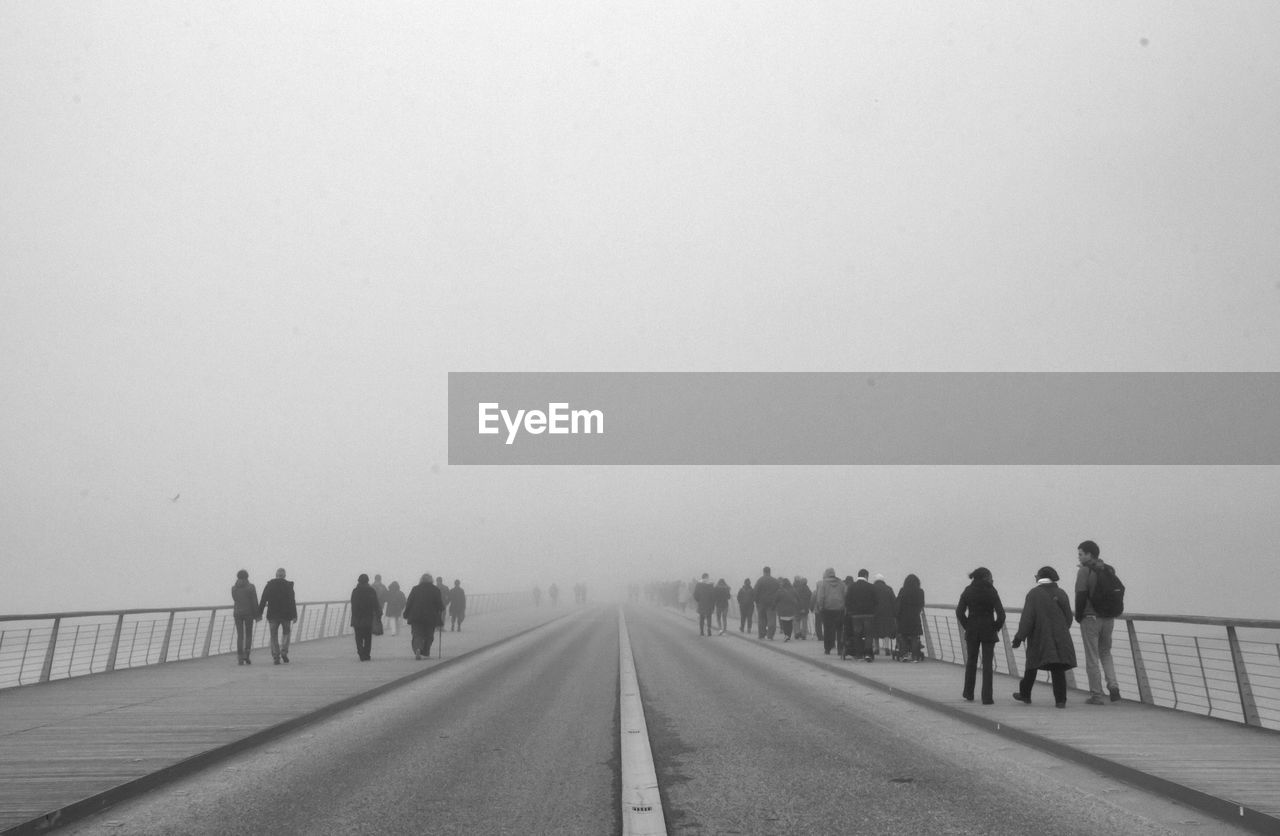People walking on road during foggy weather