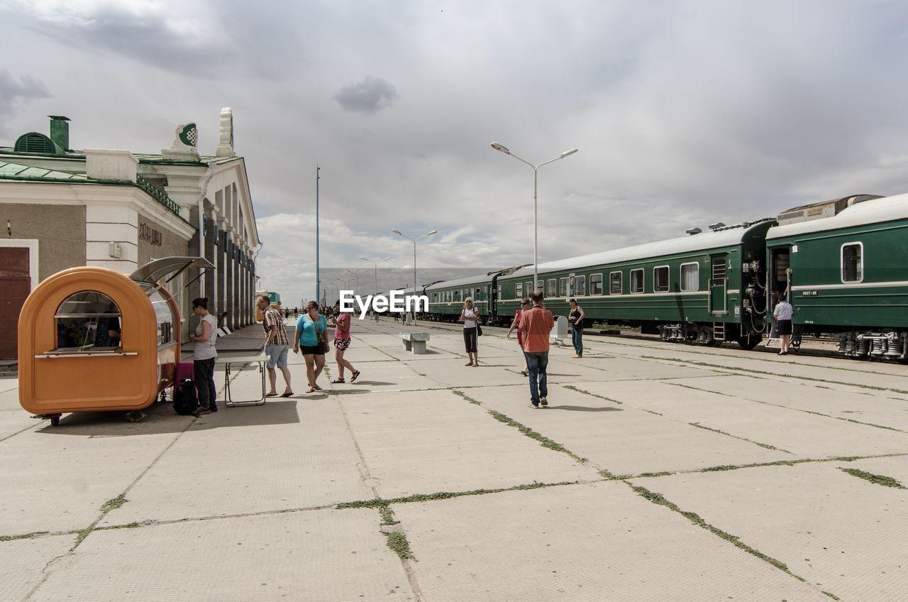 PEOPLE IN TRAIN AGAINST SKY IN CITY