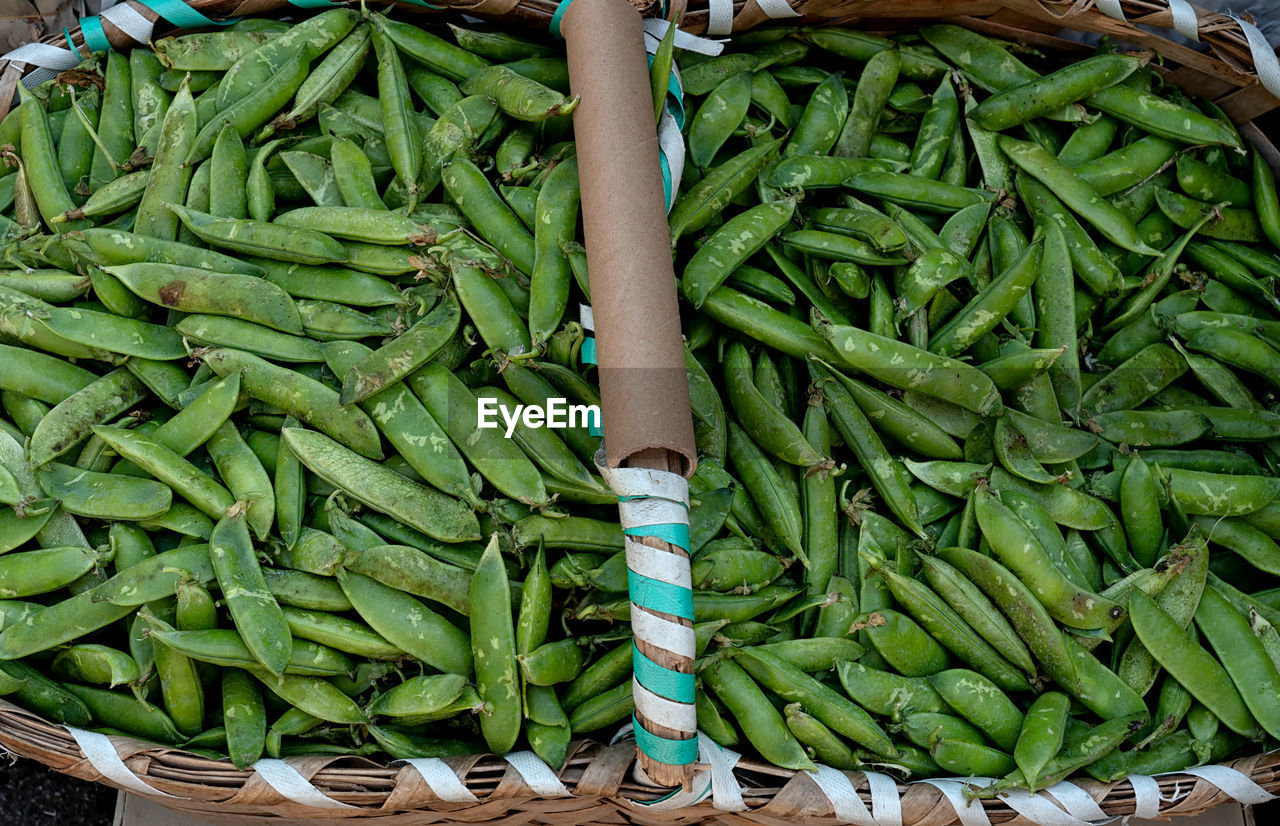 green color, market, one person, vegetable, real people, large group of objects, abundance, retail, healthy eating, for sale, food, market stall, day, business, food and drink, freshness, wellbeing, low section, human body part, human foot, human limb