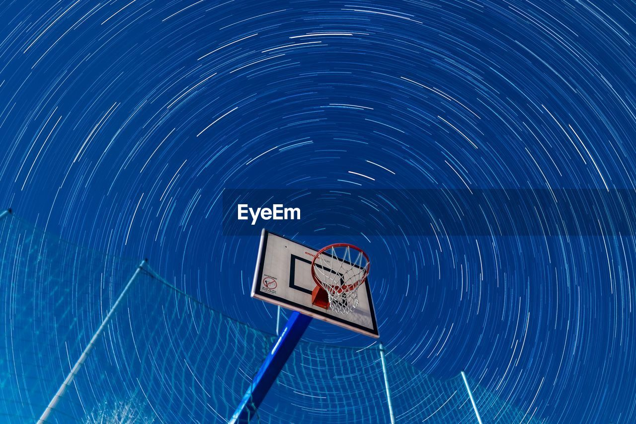 Low angle view of basketball hoop against star trails