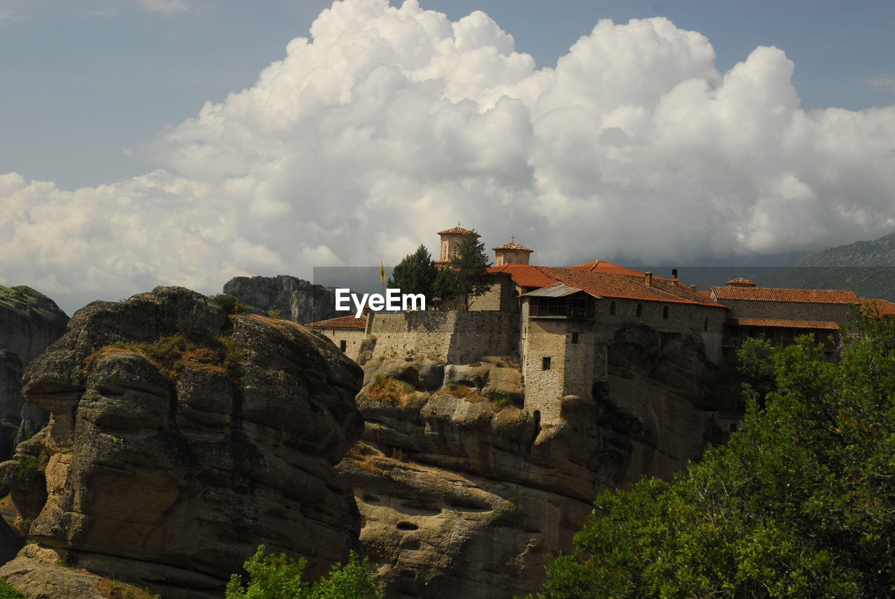 LOW ANGLE VIEW OF BUILDINGS AND MOUNTAIN AGAINST SKY