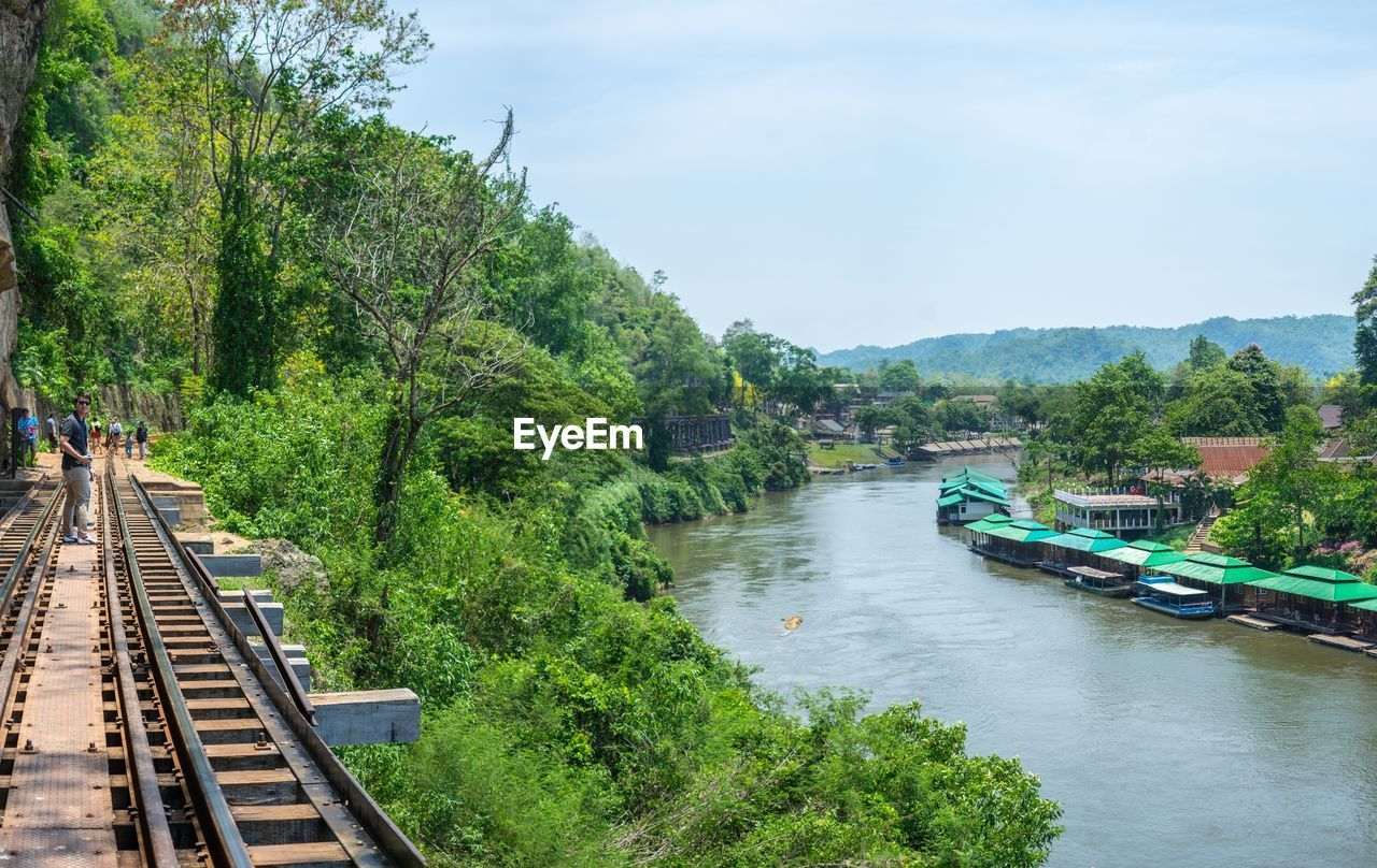 tree, transportation, plant, mode of transportation, water, sky, nature, nautical vessel, day, rail transportation, green color, public transportation, growth, travel, river, incidental people, beauty in nature, outdoors, track