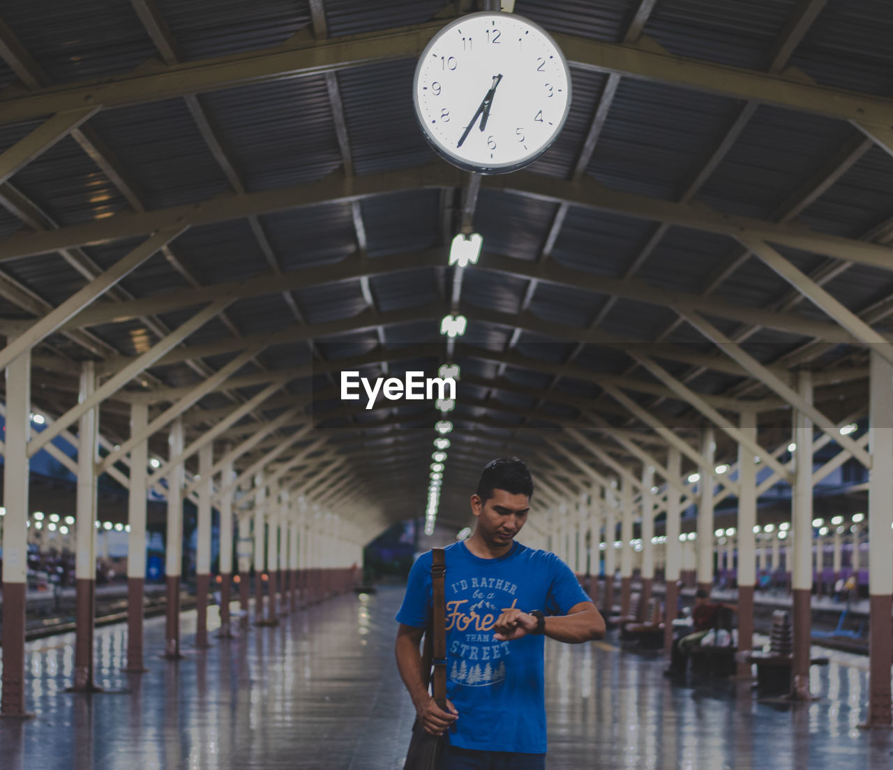 time, clock, one person, front view, real people, indoors, architecture, standing, railroad station, young adult, lifestyles, built structure, casual clothing, men, illuminated, transportation, instrument of time, three quarter length, young men, ceiling, waiting