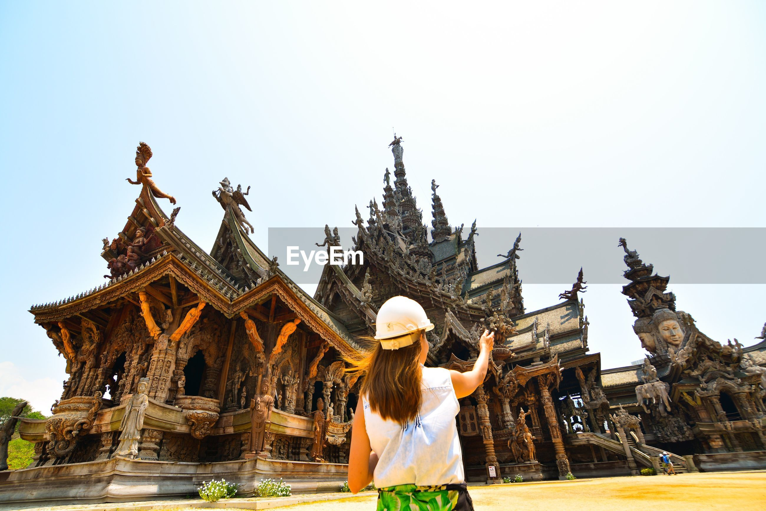 Rear view of woman on field at temple