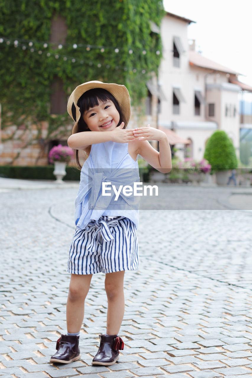 Full Length Portrait Of Smiling Girl Gesturing Outdoors
