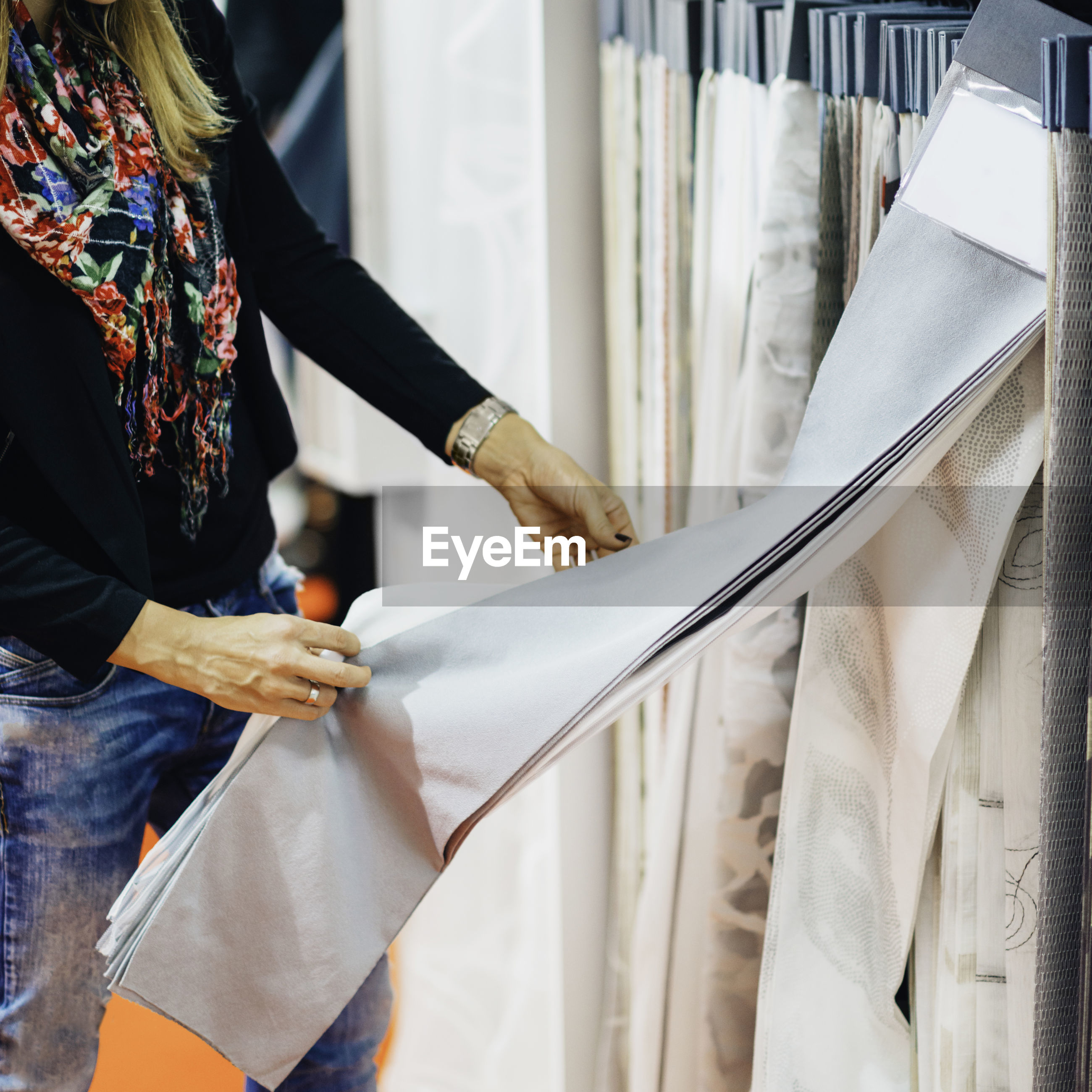 Midsection of woman holding fabric while standing in store