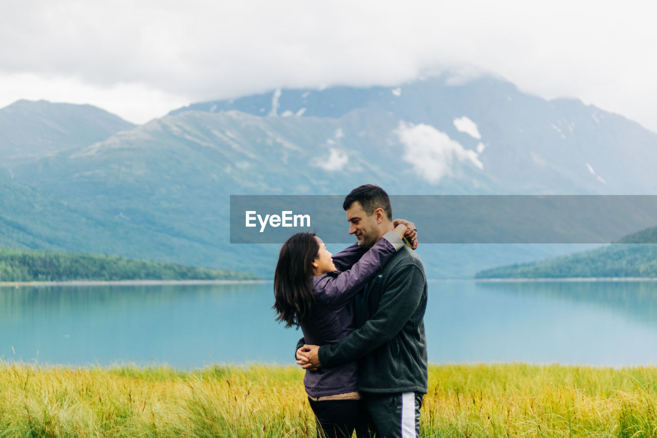 Full length of couple on lake against mountains