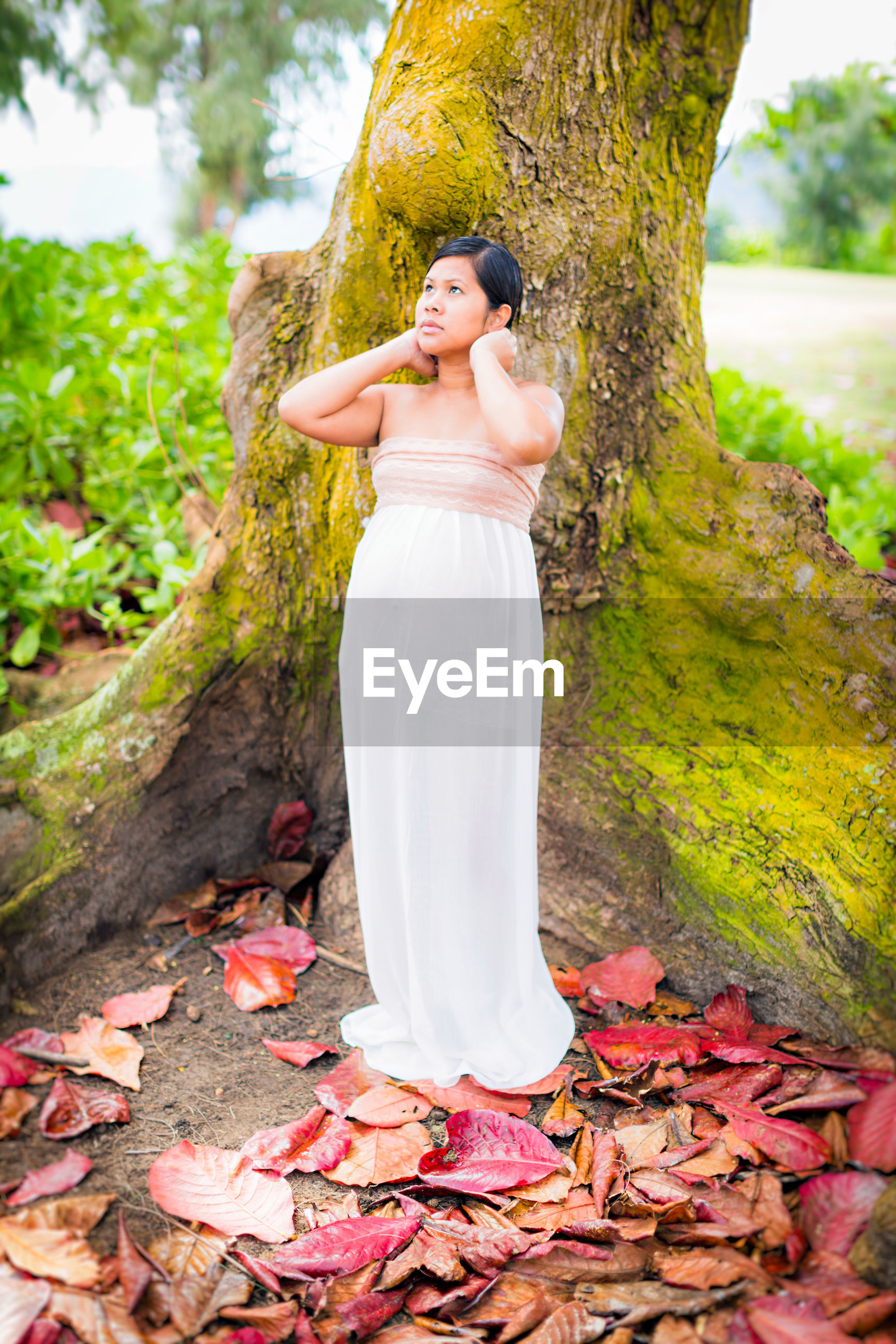 Full length of thoughtful pregnant woman standing against tree trunk