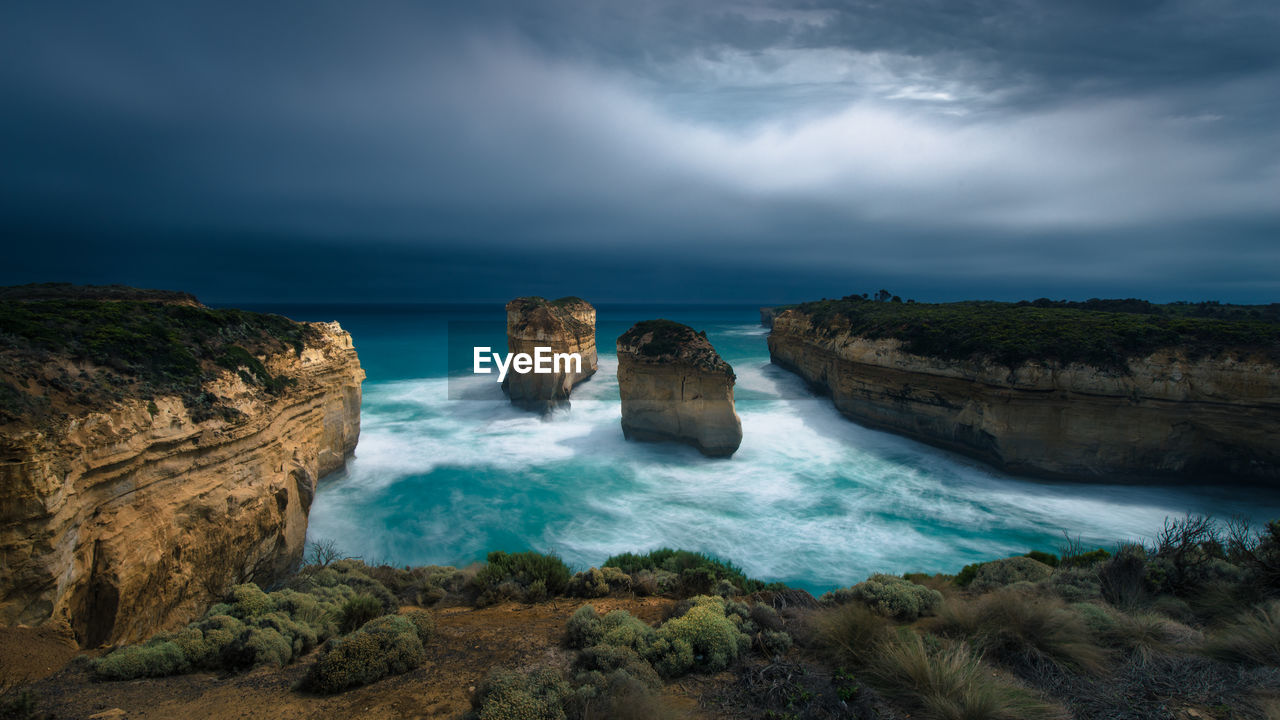 Scenic View Of Sea And Rock Formations Against Dramatic Sky